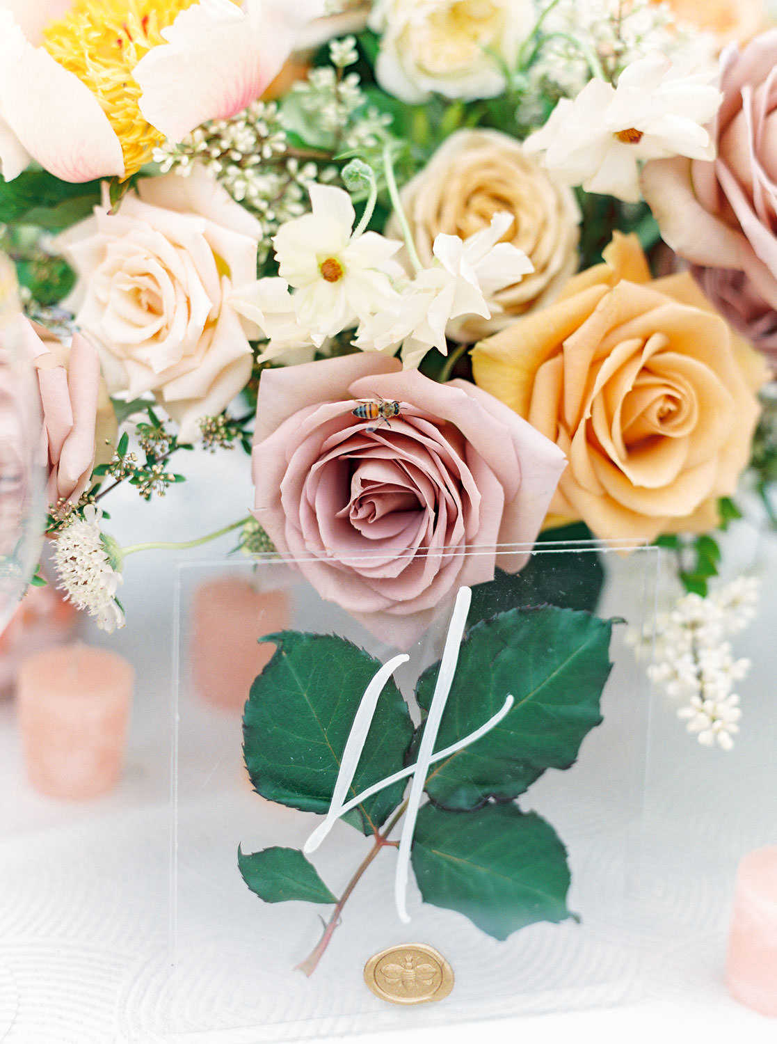 Bee on a lush centerpieces with mauve, ivory, and melon roses with greenery. Honey and Beekeeper Inspired Wedding at Rancho Valencia on film by Cavin Elizabeth Photography