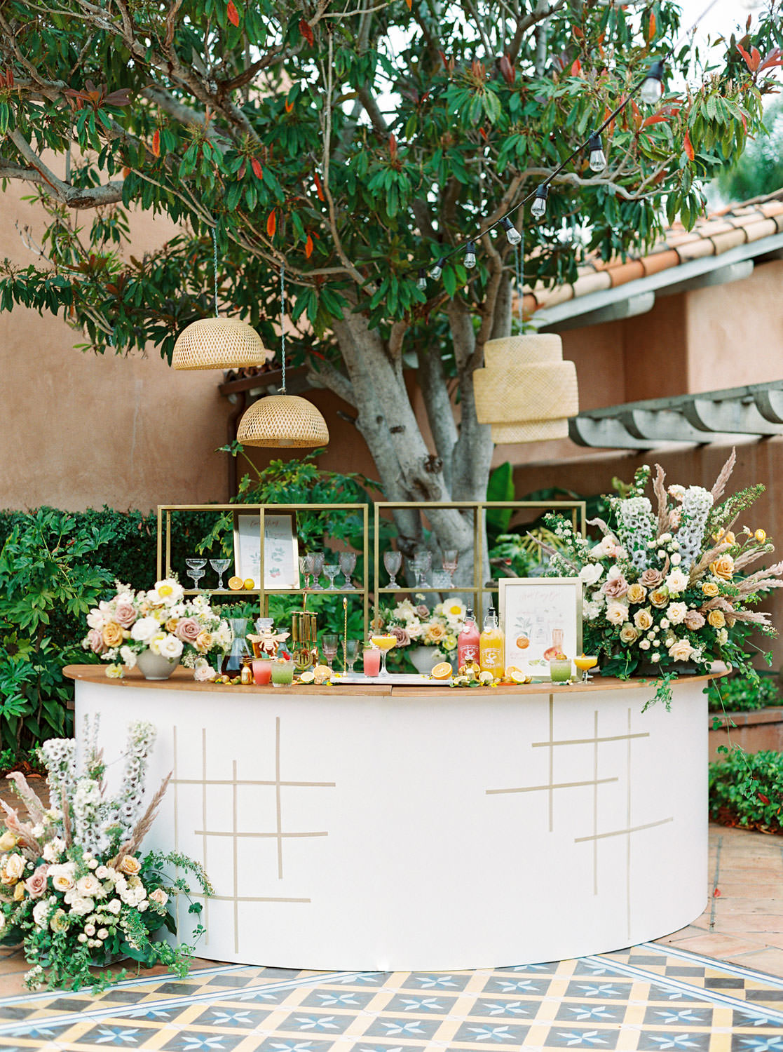 Semicircle white bar designed wild overgrown floor arrangements of yellow, mauve, and ivory flowers with organic greenery and dried pampas grass. Golden grid pattern along the bar front using a gold foil hexagon tape. Beekeeper Inspired Wedding at Rancho Valencia on film by Cavin Elizabeth Photography