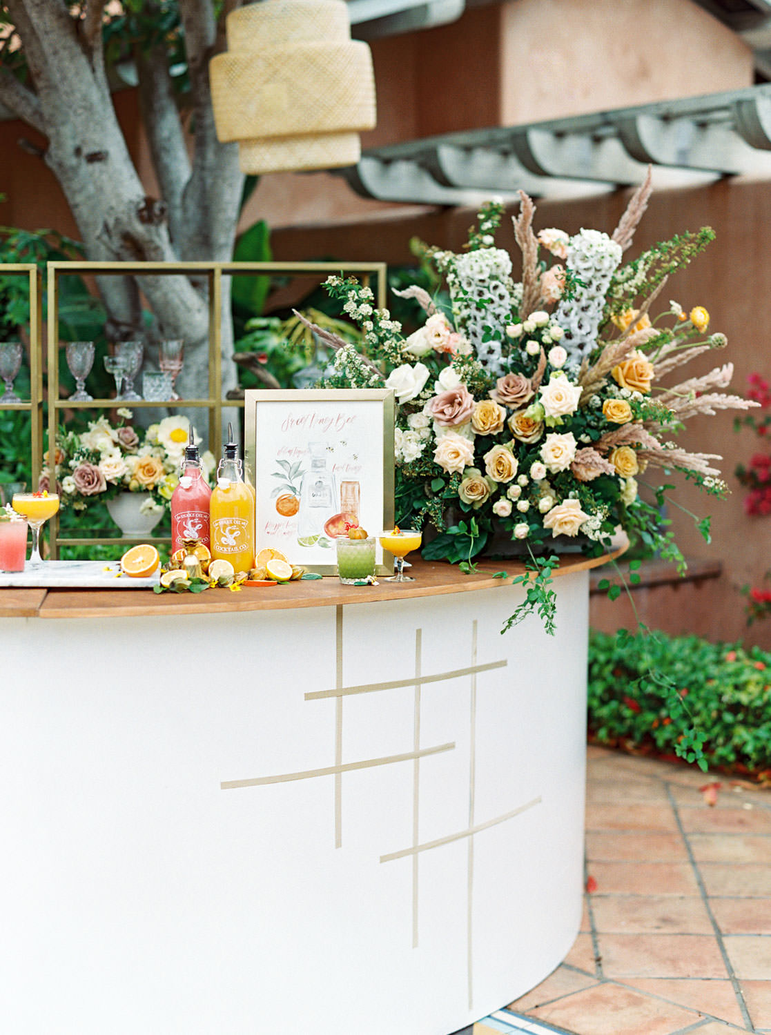 Semicircle white bar designed wild overgrown floor arrangements of yellow, mauve, and ivory flowers with organic greenery and dried pampas grass. Golden grid pattern along the bar front using a gold foil hexagon tape. Yellow, pink, and green craft cocktails and watercolor bar sign with cocktail illustration. Beekeeper Inspired Wedding at Rancho Valencia on film by Cavin Elizabeth Photography