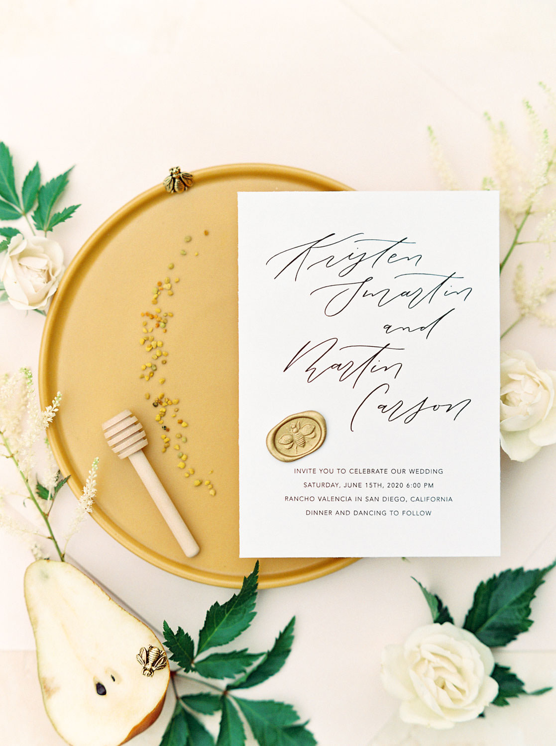White wedding invitation with black ink and golden bee waxseal styled on a golden plate with bee pollen, honey, and greenery. Honey and Beekeeper Inspired Wedding at Rancho Valencia on film by Cavin Elizabeth Photography