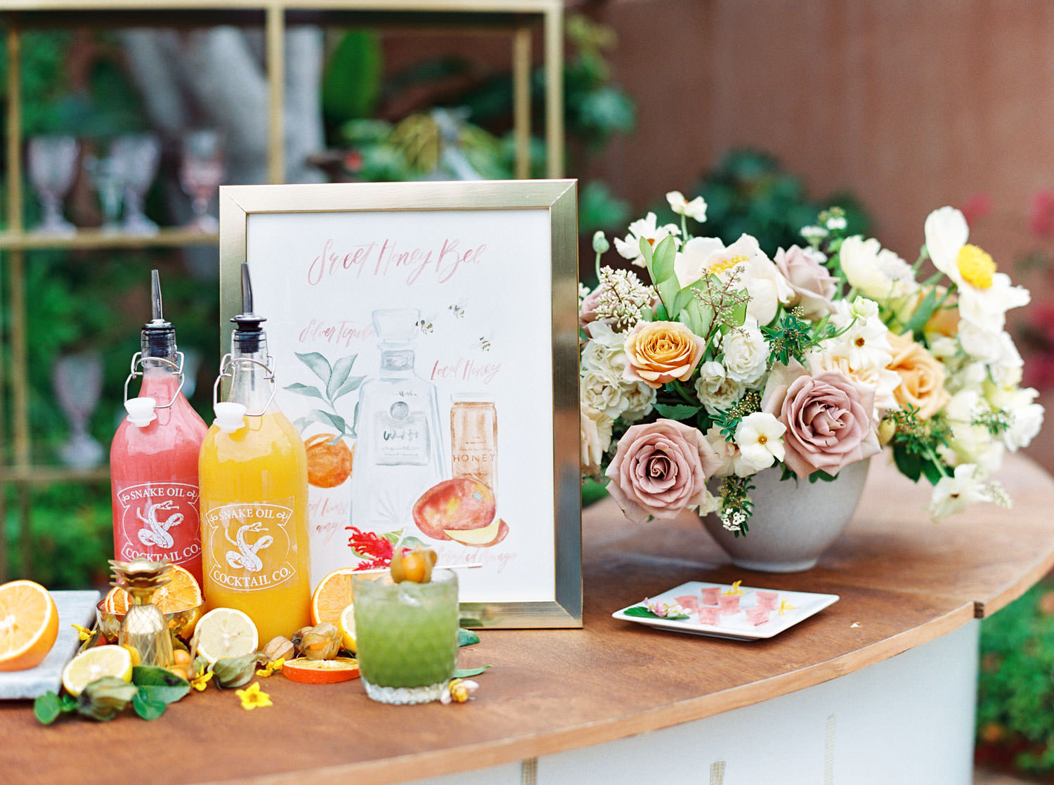 Yellow, pink, and green craft cocktails and watercolor bar sign with cocktail illustration next to floral arrangement with mauve, yellow, ivory, and green flowers. Beekeeper Inspired Wedding at Rancho Valencia on film by Cavin Elizabeth Photography