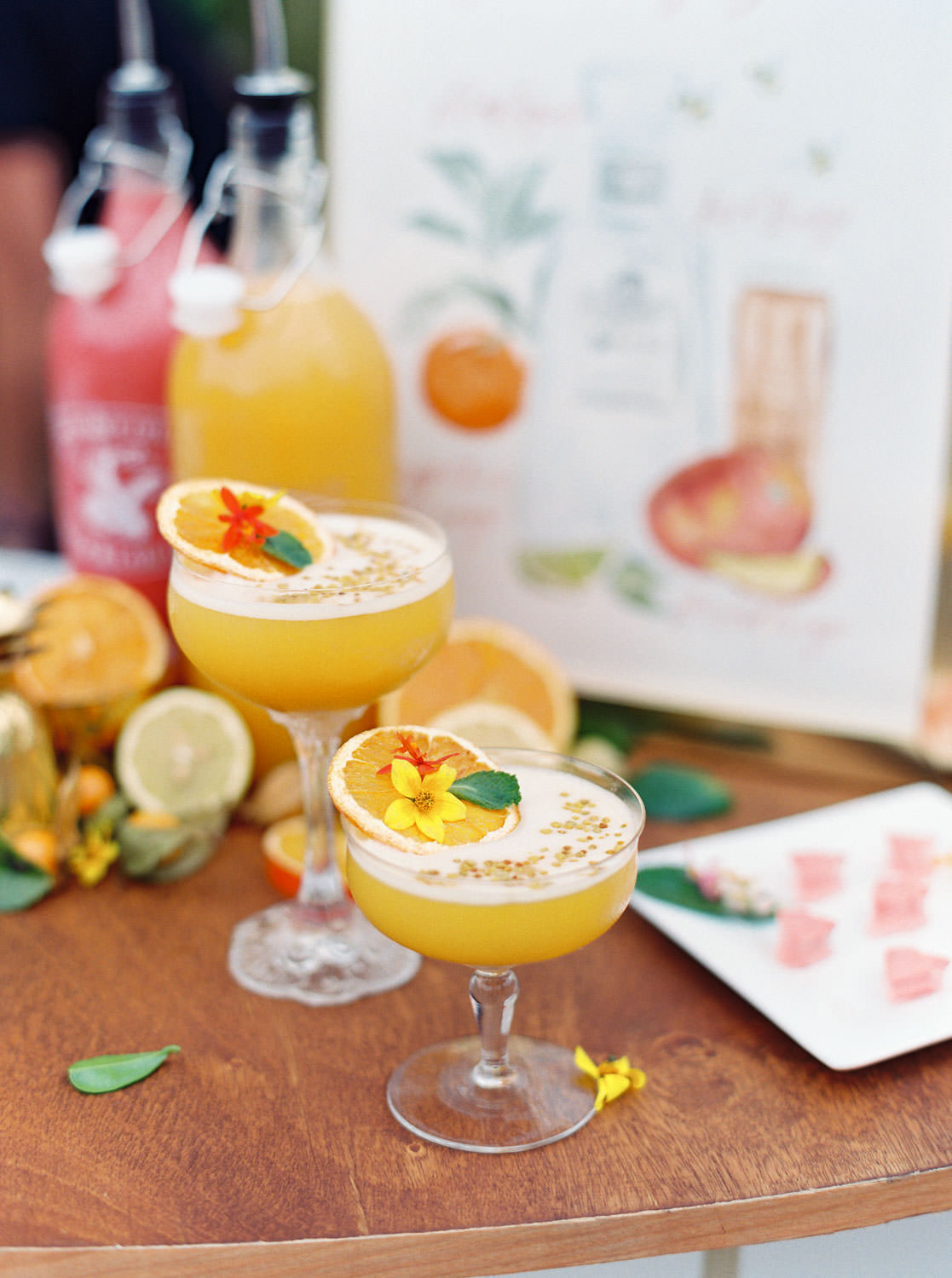 Golden yellow craft cocktails with bee pollen and orange slice garnish served in coupes. Beekeeper Inspired Wedding at Rancho Valencia on film by Cavin Elizabeth Photography