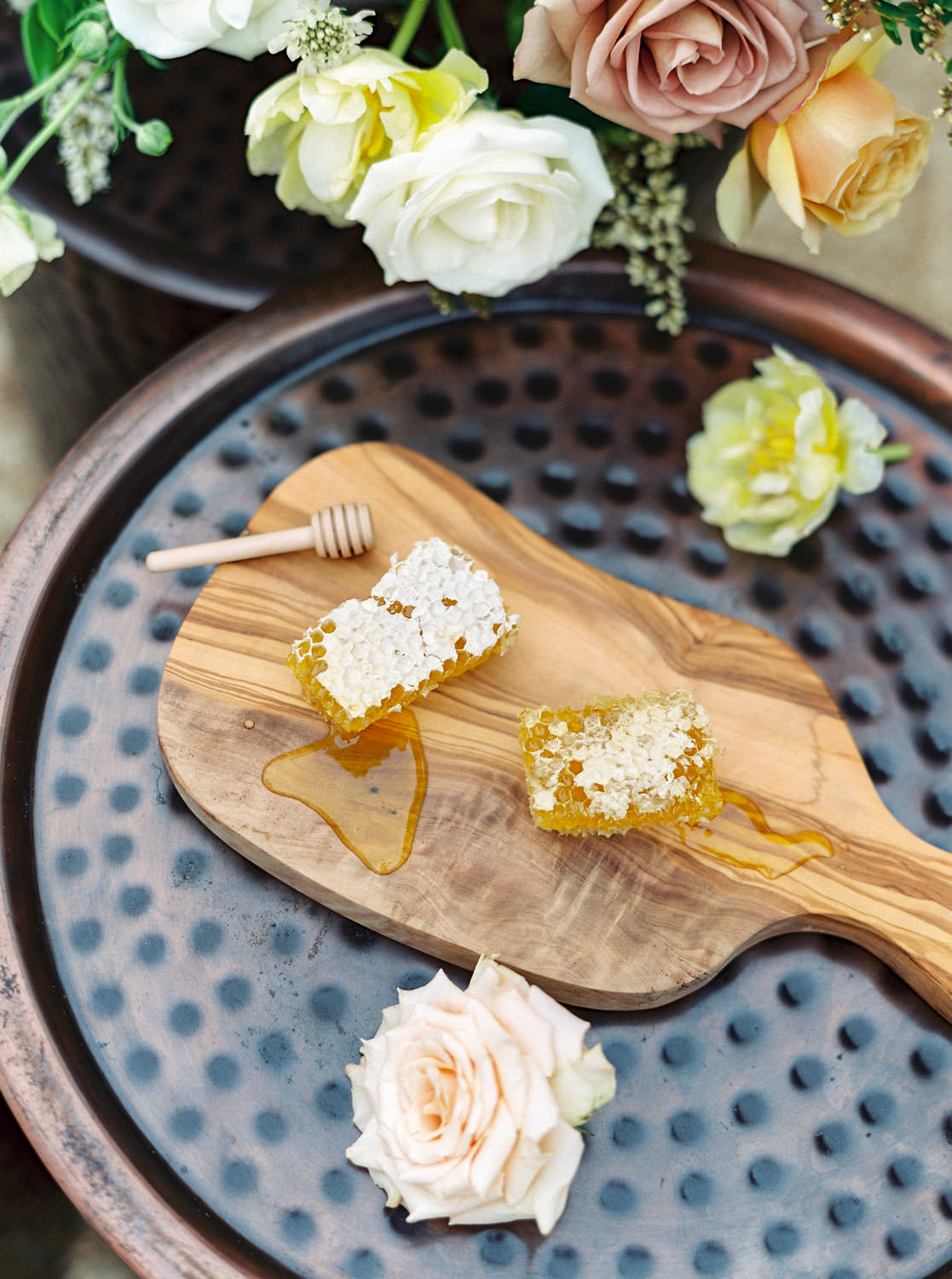 Trio of dark brown coffee tables. Honeycombs and honey styled on a wooden cheese board with a honey dipper. Bee and honey themed wedding that's sophisticated and elegant. Beekeeper Inspired Wedding at Rancho Valencia on film by Cavin Elizabeth Photography