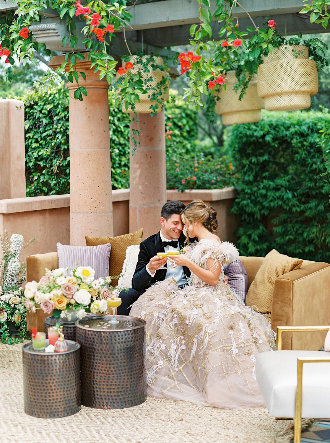 Bride and groom sipping cocktails in Wedding lounge with golden brown sofa and ivory armchairs with gold frames. Trio of dark brown coffee tables. floral arrangement with mauve, yellow, ivory, and green flowers. Beekeeper Inspired Wedding at Rancho Valencia on film by Cavin Elizabeth Photography