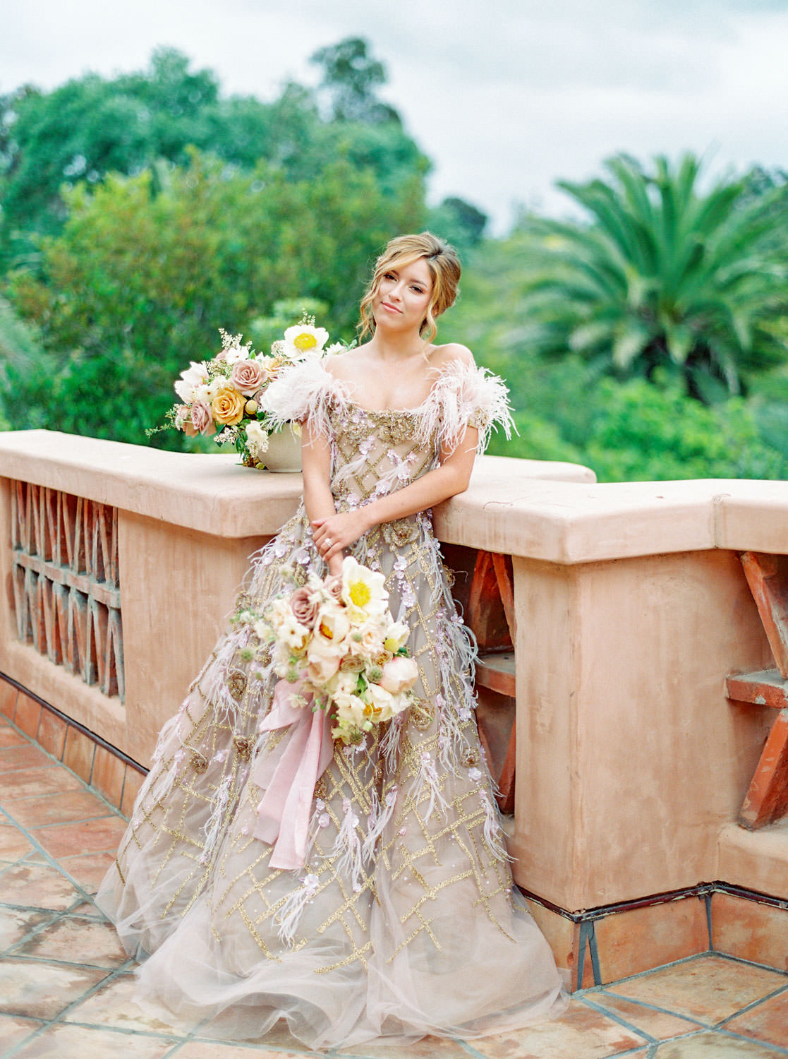 Bridal bouquet with mauve, ivory, yellow roses and greenery with trailing blush ribbons. Marchesa couture gown with blush feathers, gold lines, and floral embellishments. Honey and Beekeeper Inspired Wedding at Rancho Valencia on film by Cavin Elizabeth Photography
