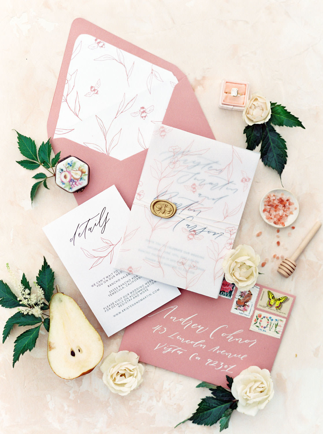 Mauve wedding envelopes with white ink and an ivory wedding invitation suite with floral vellum and envelope liner styled with pears, roses, greenery, rings, and pink salt. Honey and Beekeeper Inspired Wedding at Rancho Valencia on film by Cavin Elizabeth Photography
