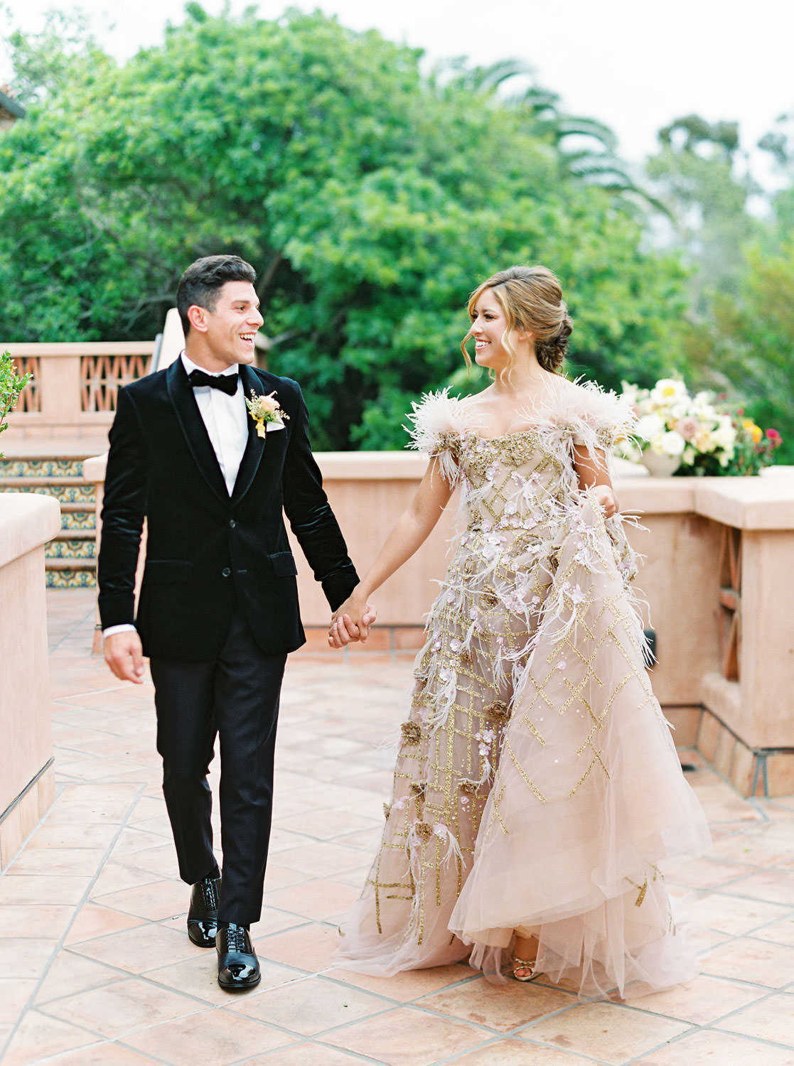 Groom in black velvet tuxedo walking with bride wearing a Marchesa couture gown with blush feathers, gold lines, and floral embellishments. Honey and Beekeeper Inspired Wedding at Rancho Valencia on film by Cavin Elizabeth Photography