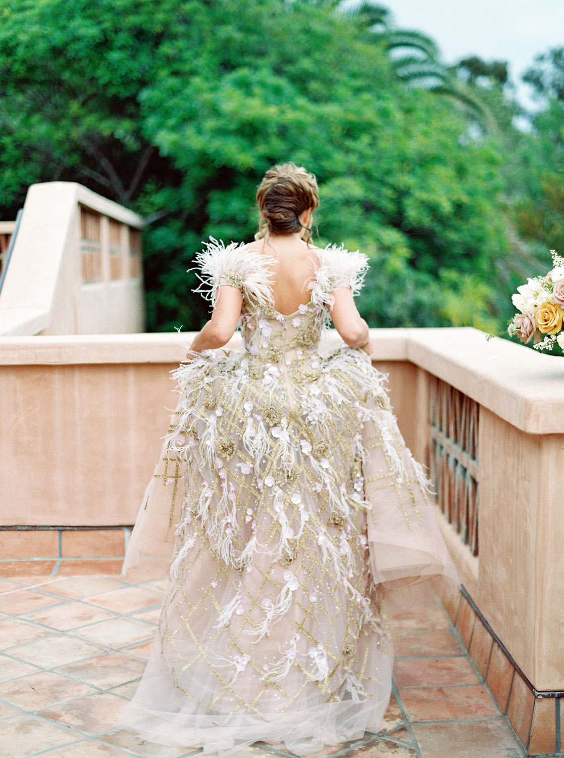 Bride running wearing a Marchesa couture gown with blush feathers, gold lines, and floral embellishments. Honey and Beekeeper Inspired Wedding at Rancho Valencia on film by Cavin Elizabeth Photography