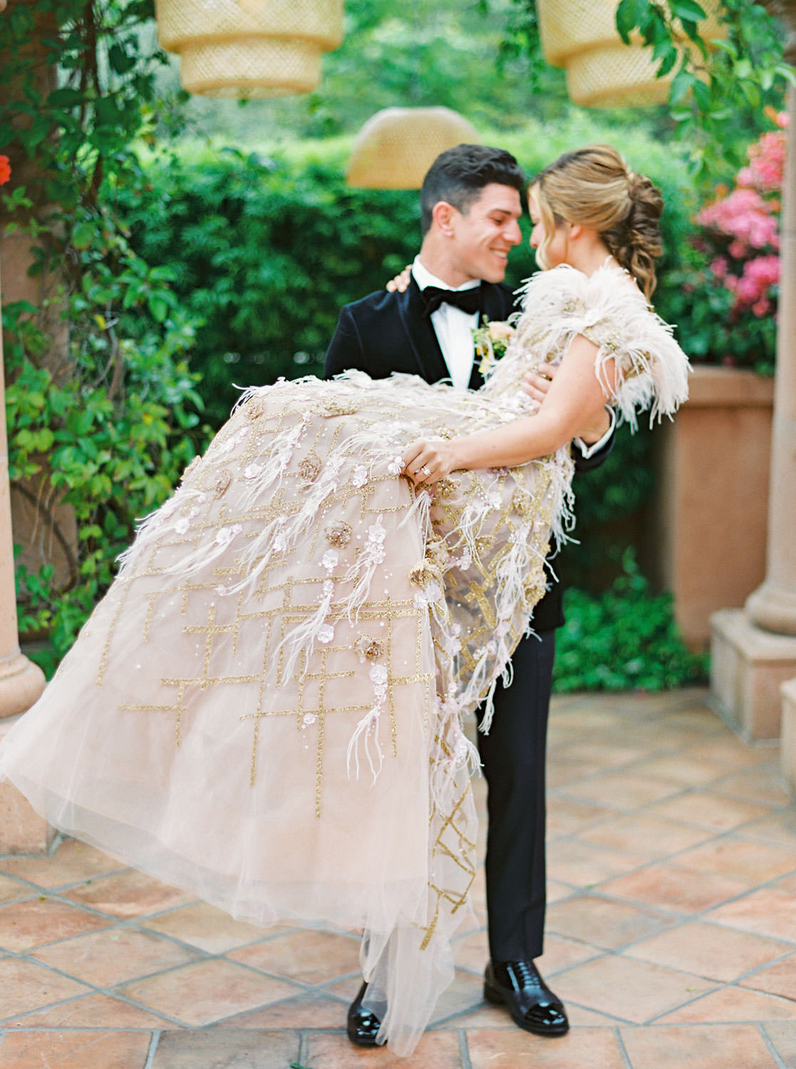 Groom in black velvet tuxedo carrying bride wearing a Marchesa couture gown with blush feathers, gold lines, and floral embellishments. Honey and Beekeeper Inspired Wedding at Rancho Valencia on film by Cavin Elizabeth Photography