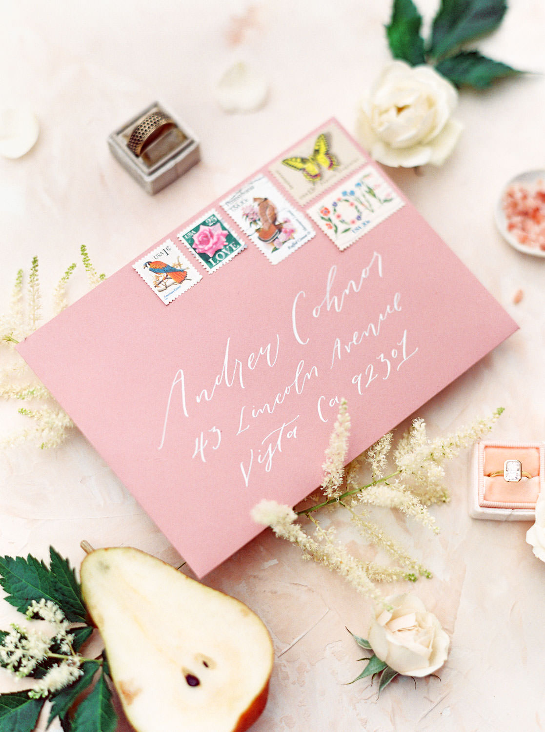 Mauve wedding envelopes with white ink styled with pears, roses, greenery, rings, and pink salt. Honey and Beekeeper Inspired Wedding at Rancho Valencia on film by Cavin Elizabeth Photography
