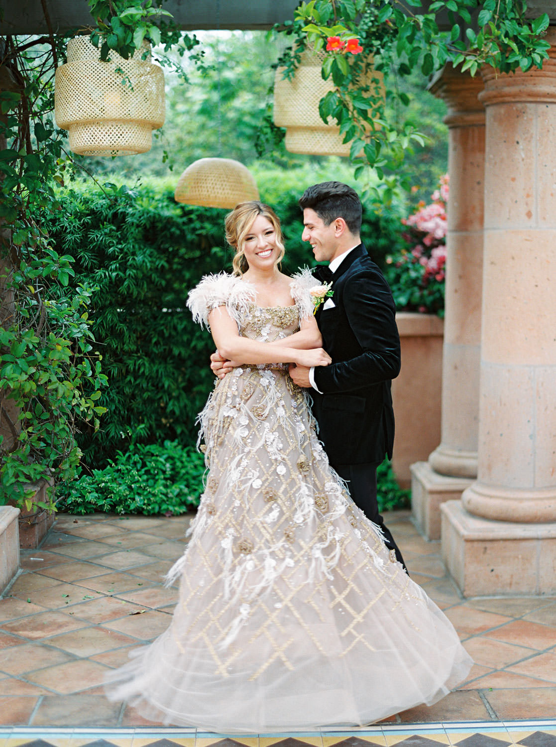 Groom in black velvet tuxedo dancing with bride wearing a Marchesa couture gown with blush feathers, gold lines, and floral embellishments. Honey and Beekeeper Inspired Wedding at Rancho Valencia on film by Cavin Elizabeth Photography