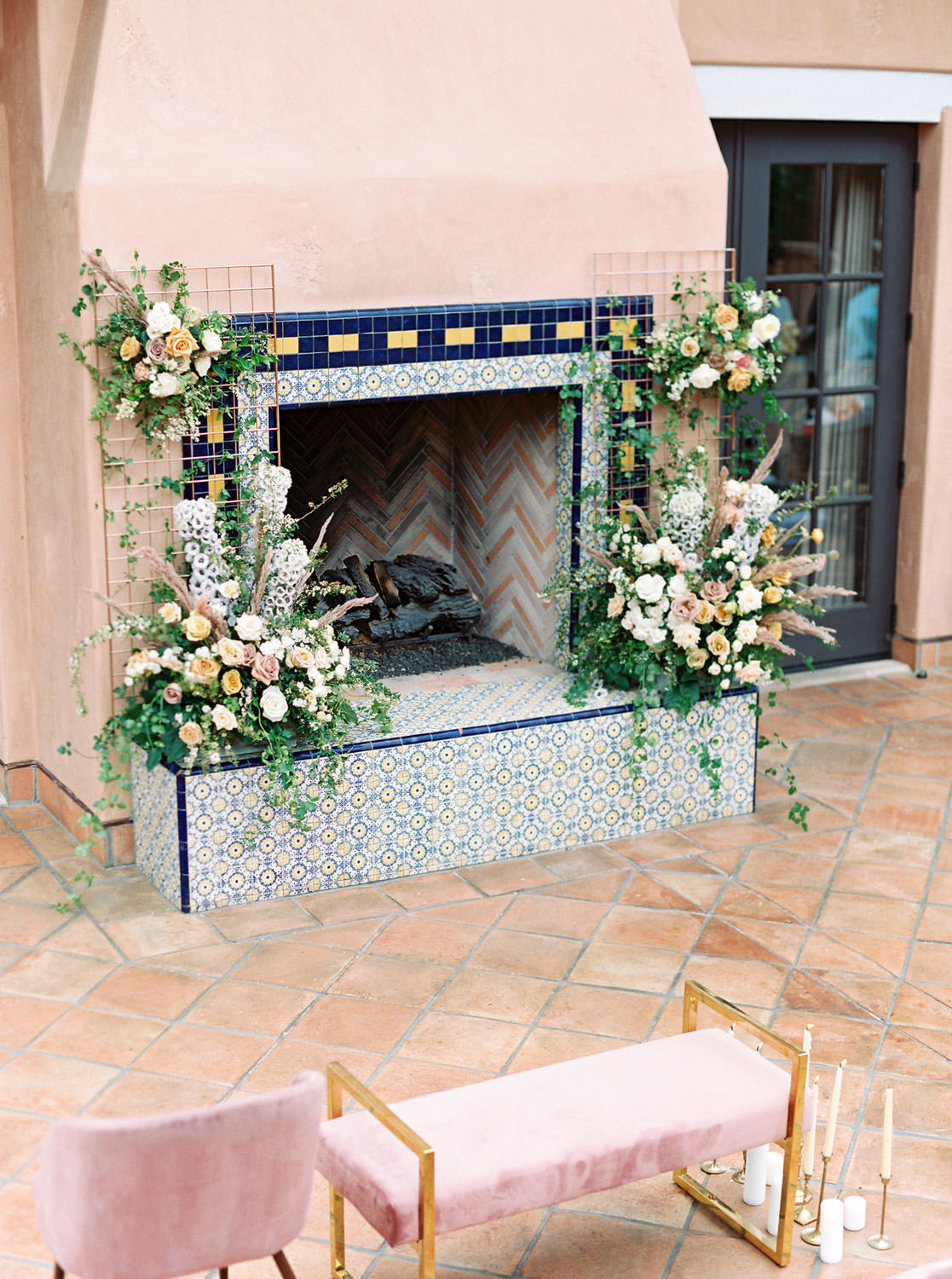 Pink fireplace with blue and golden tiles for ceremony backdrop adorned with large floral installations. Mauve blush velvet chairs and bench for ceremony seating. Honey and Beekeeper Inspired Wedding on sunrise terrace patio at Rancho Valencia on film by Cavin Elizabeth Photography