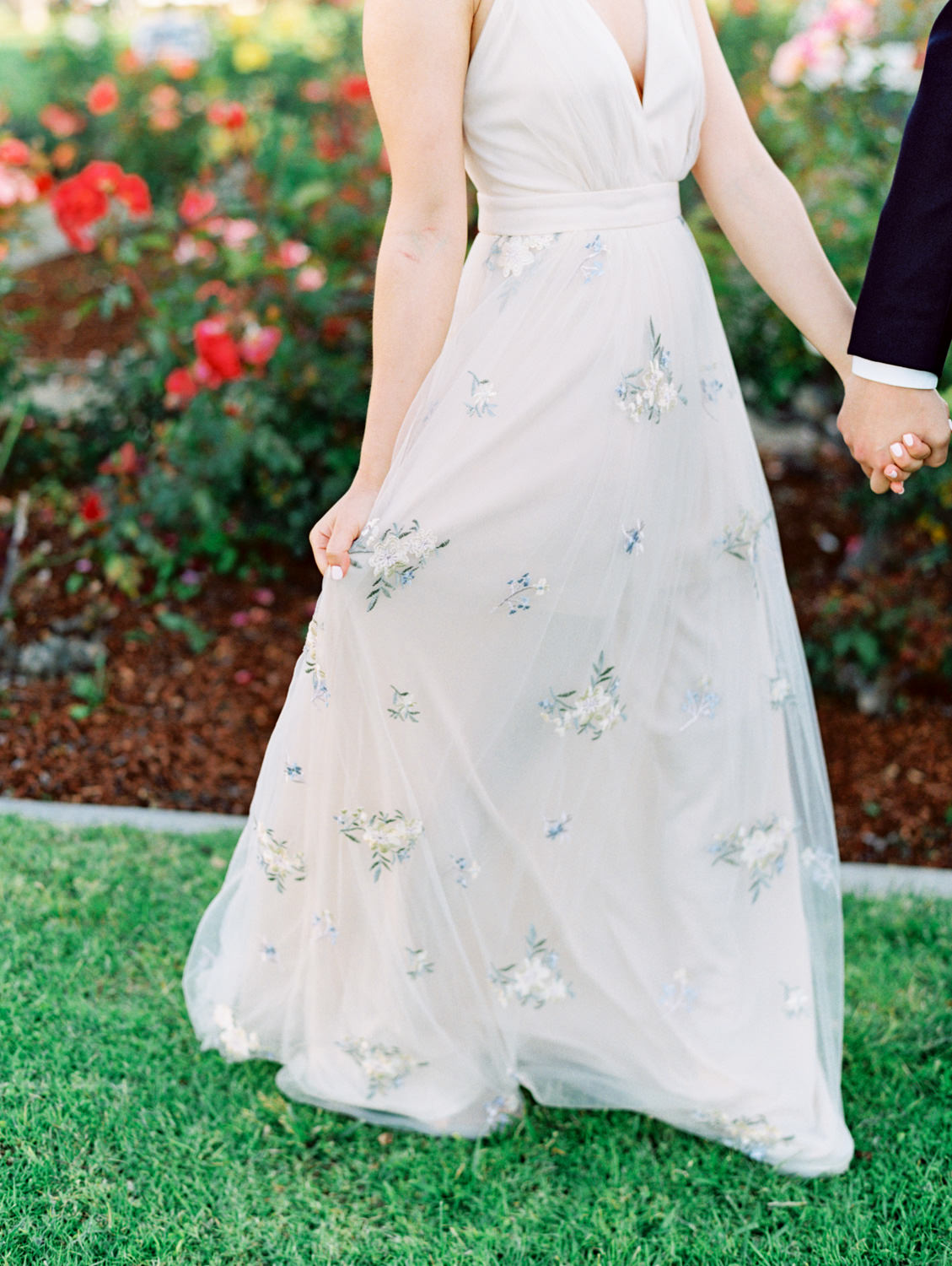 Bride with ivory and blush rose bouquet and floral print dress and groom in suit and tie in front of a rose garden. Coronado Centennial Park Engagement Photo by Cavin Elizabeth Photography - San Diego film photographer