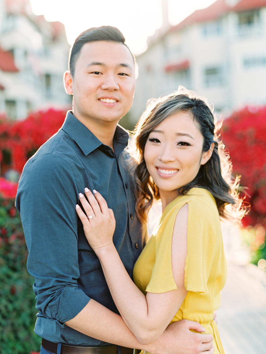 Bride in golden yellow dress with groom smiling at the camera in front of a large pink bougainvillea bush in Coronado Centennial Park by Cavin Elizabeth Photography - San Diego film photographer