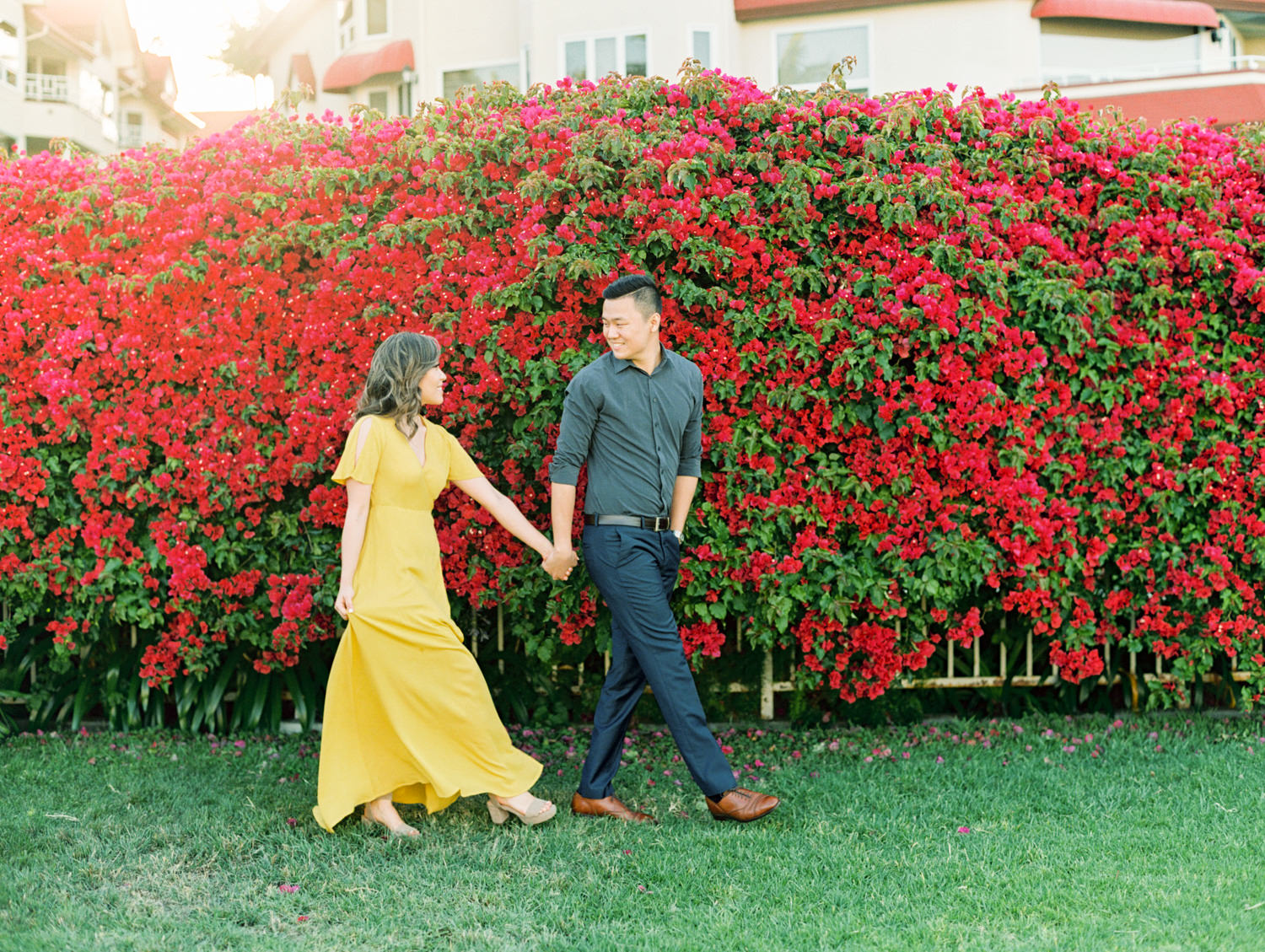 Bride in golden yellow dress with groom in front of a large pink bougainvillea bush. Coronado Centennial Park Engagement Photo by Cavin Elizabeth Photography - San Diego film photographer