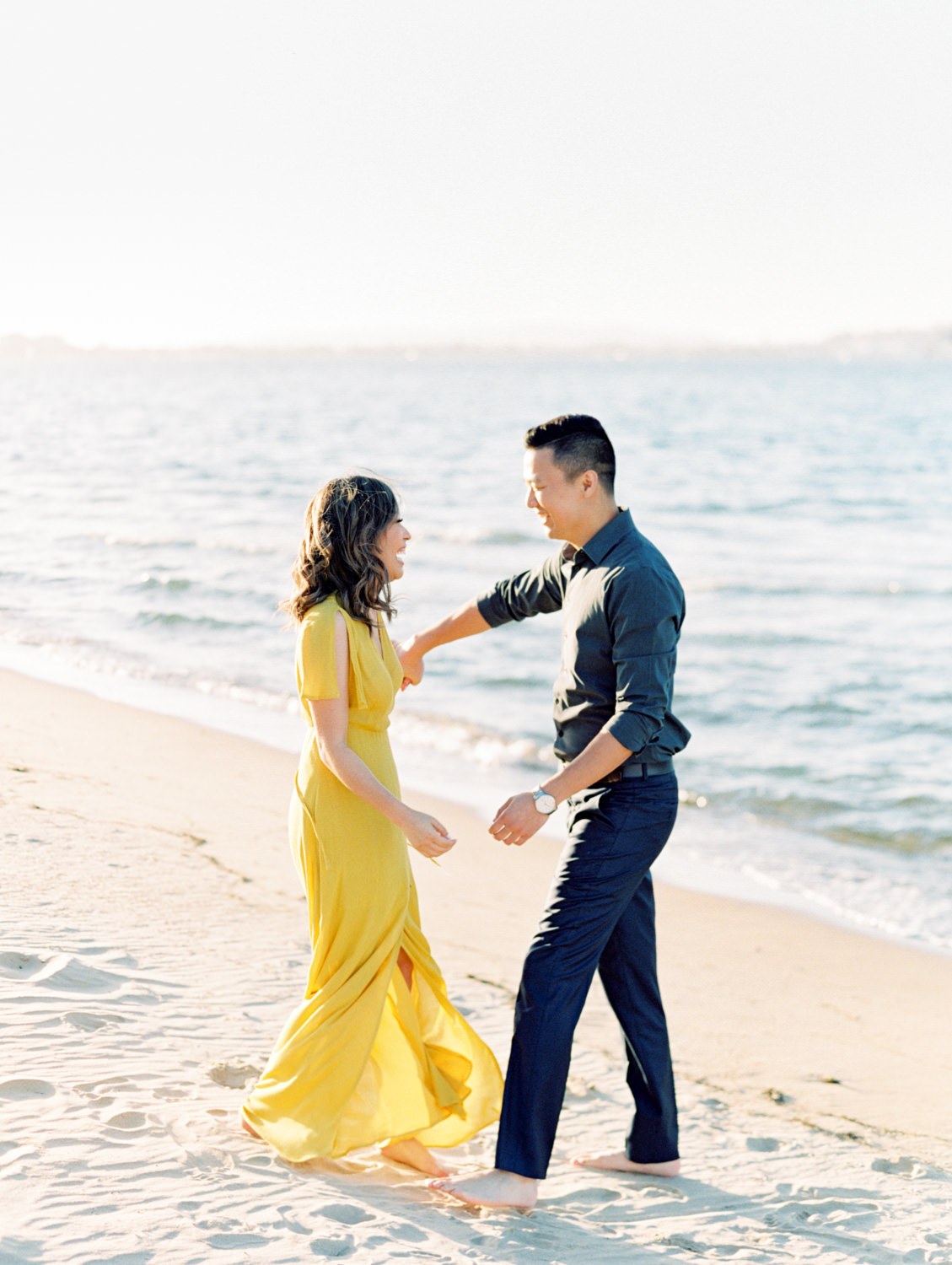 Bride in golden yellow dress with groom running on the beach in Coronado. Cavin Elizabeth Photography - San Diego film photographer