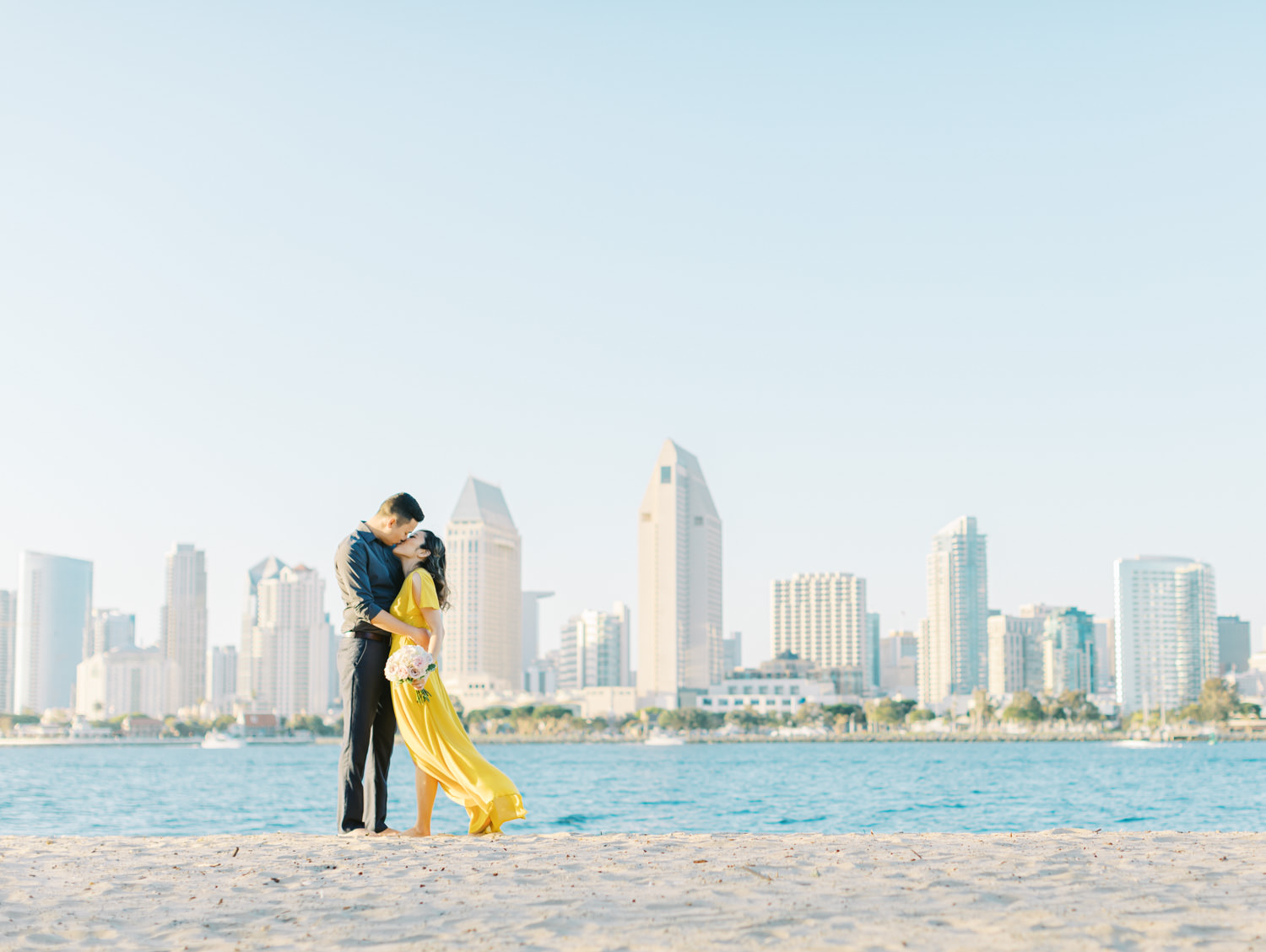 Bride in golden yellow dress with groom in front of the San Diego skyline. Cavin Elizabeth Photography