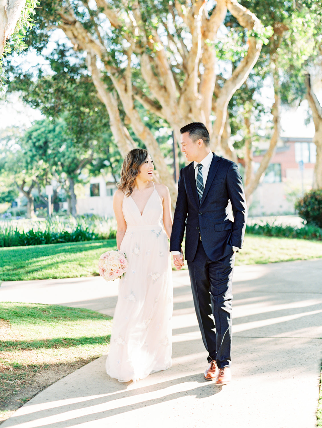 Bride with ivory and blush rose bouquet and floral print dress and groom in suit and tie. Coronado Centennial Park Engagement Photo by Cavin Elizabeth Photography - San Diego film photographer