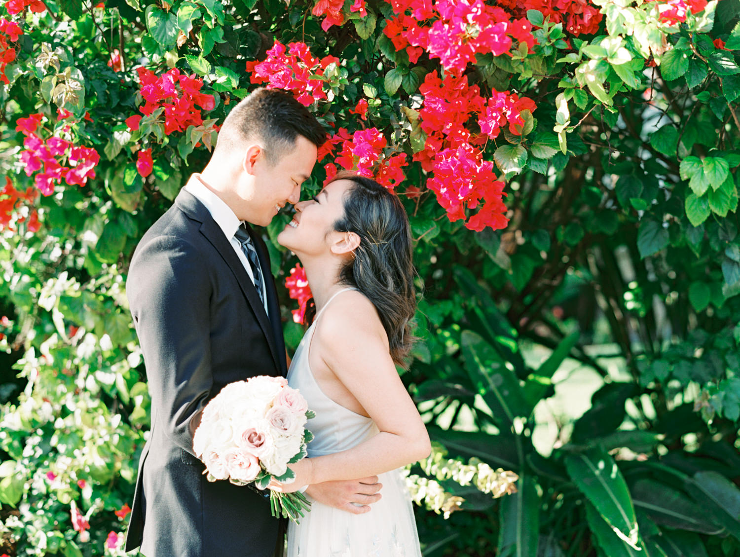 Bride with ivory and blush rose bouquet and floral print dress and groom in suit and tie in front of a pink bougainvillea bush. Coronado Centennial Park Engagement Photo by Cavin Elizabeth Photography - San Diego film photographer