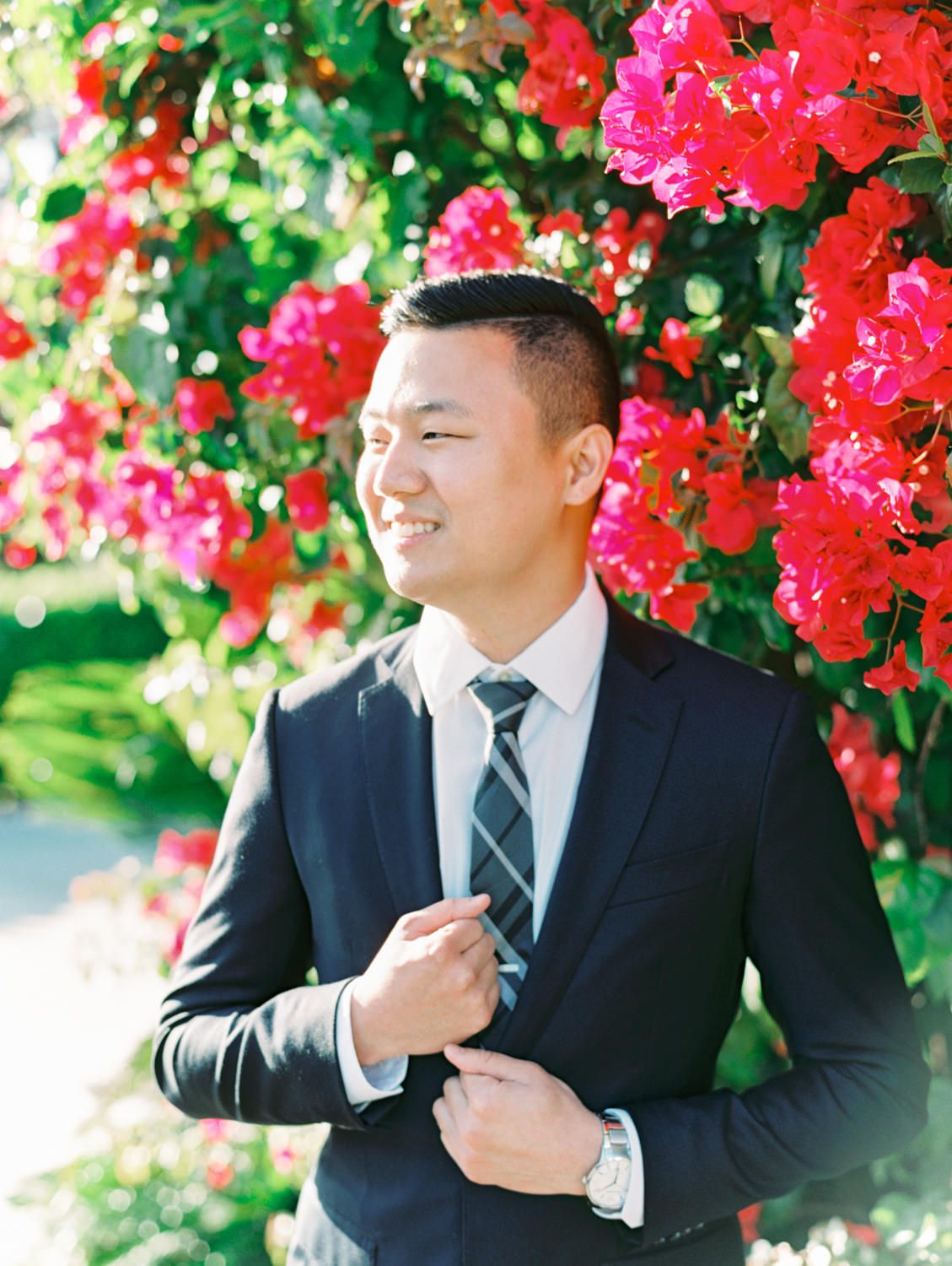 Groom in suit and tie in front of a pink bougainvillea bush. Coronado Centennial Park Engagement Photo by Cavin Elizabeth Photography - San Diego film photographer