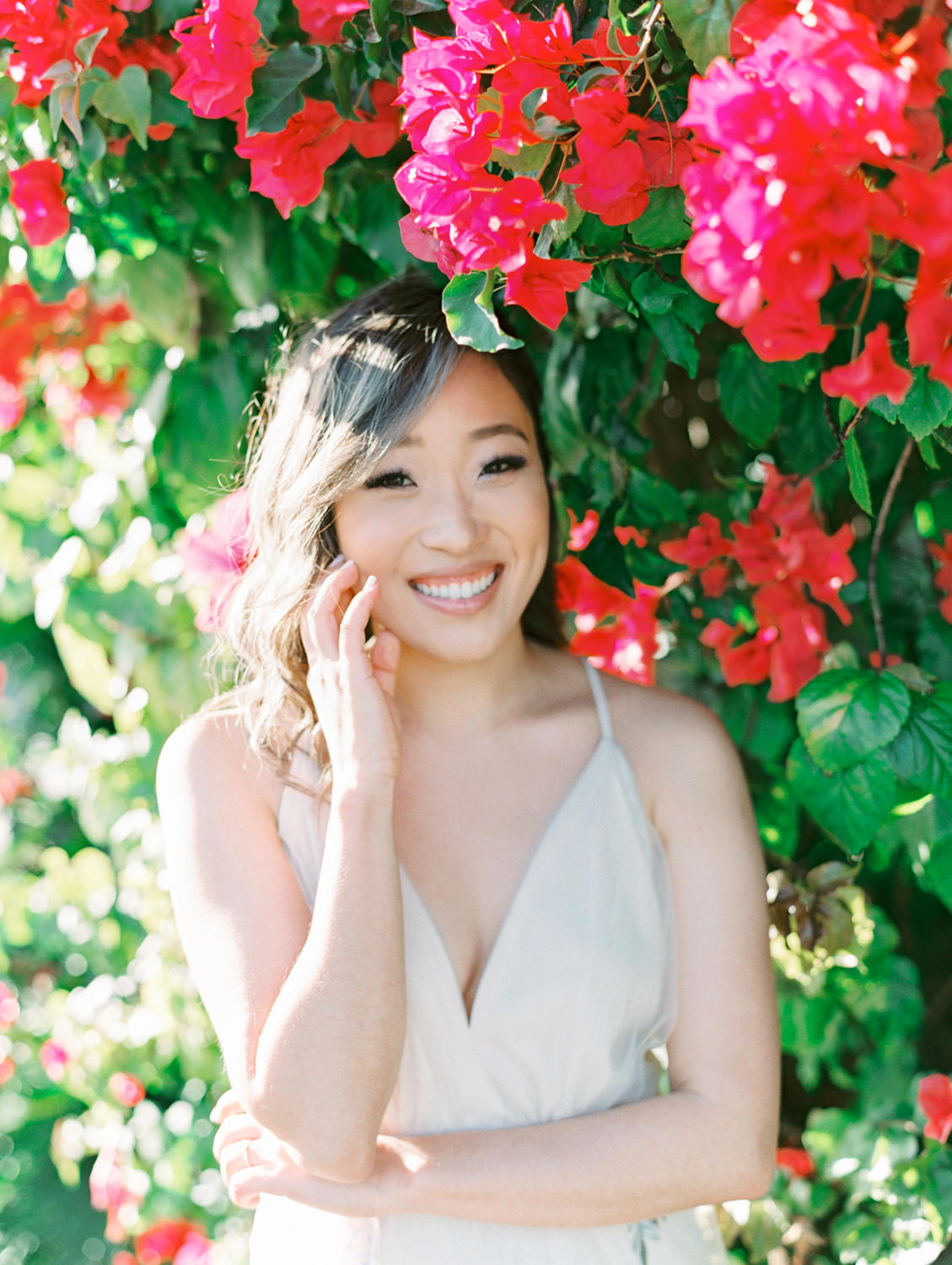 Bride wearing a neutral dress with loose curls in front of a pink bougainvillea bush. Coronado Centennial Park Engagement Photo by Cavin Elizabeth Photography - San Diego film photographer