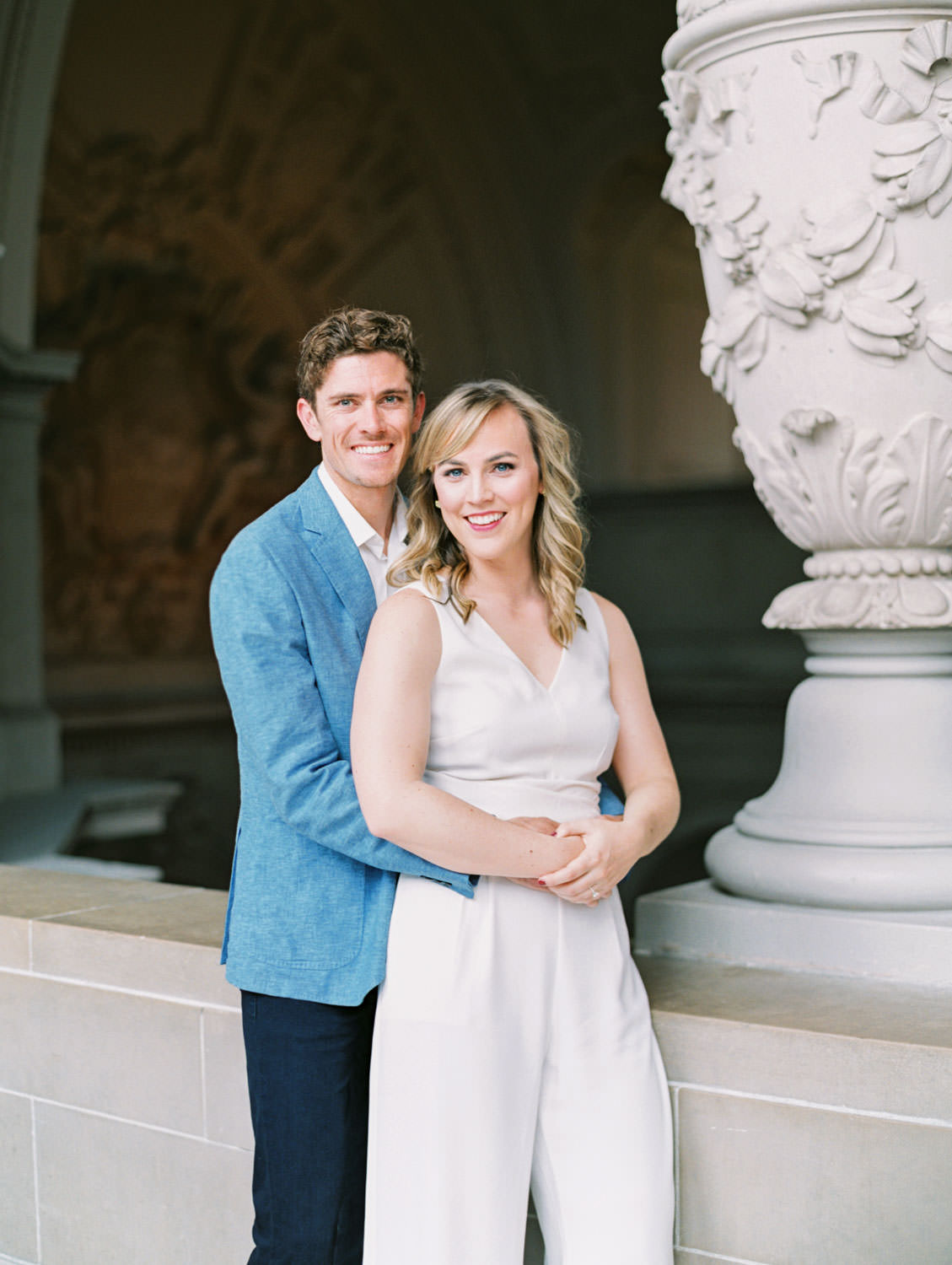 Bride in white linen jumpsuit and groom in blue blazer and dark jeans. Film Engagement Photos at San Francisco City Hall by Cavin Elizabeth