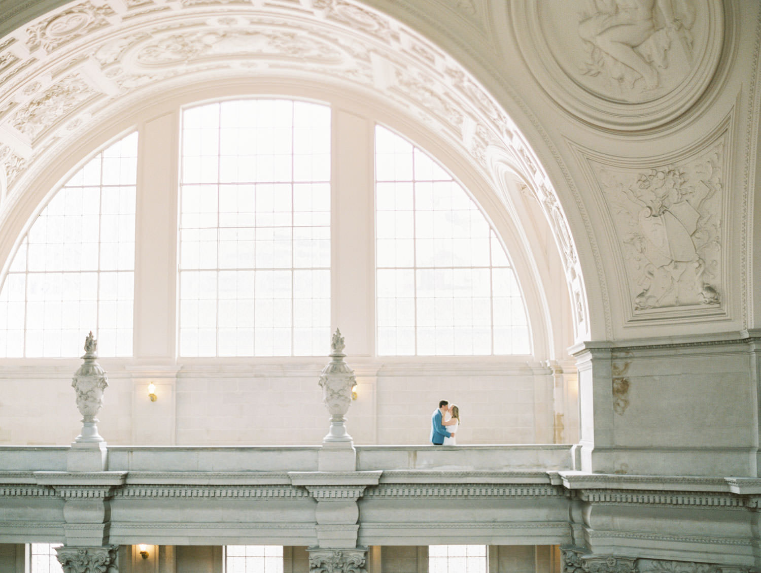 Gorgeous ultra wide shot of bride in white linen jumpsuit and groom in blue blazer and dark jeans. Film Engagement Photos at San Francisco City Hall by Cavin Elizabeth