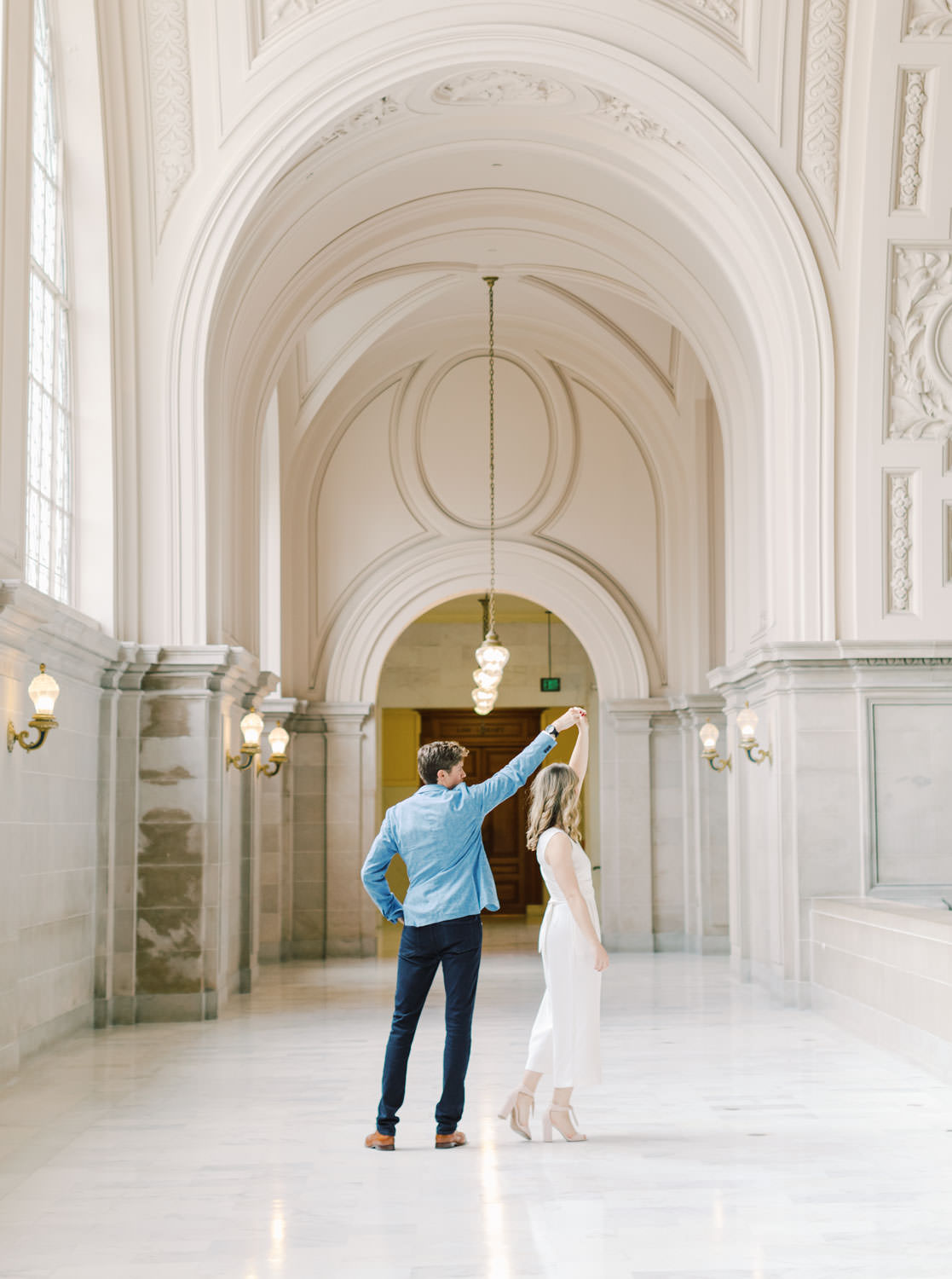 Bride in white linen jumpsuit and groom in blue blazer and dark jeans dancing on the 4th floor. Engagement Photos at San Francisco City Hall by Cavin Elizabeth