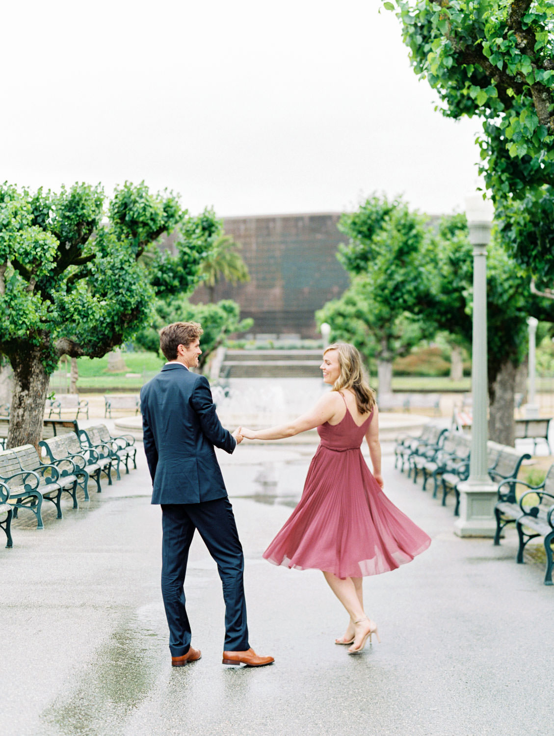 Bride in a deep mauve dress and groom in navy suit walking dancing in a park. Film Engagement Photos at Golden Gate Park by Cavin Elizabeth