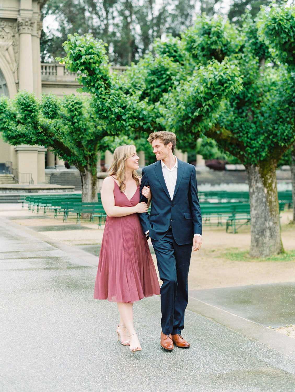 Bride in a deep mauve dress and groom in navy suit walking through a park. Film Engagement Photos at Golden Gate Park by Cavin Elizabeth