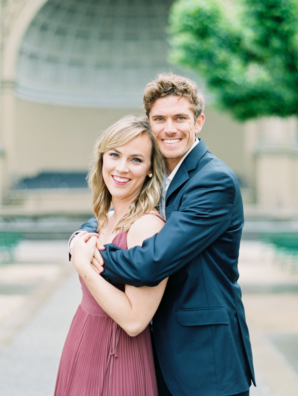 Bride in a deep mauve dress and groom in navy suit hugging and smiling at the camera. Film Engagement Photos at Golden Gate Park by Cavin Elizabeth