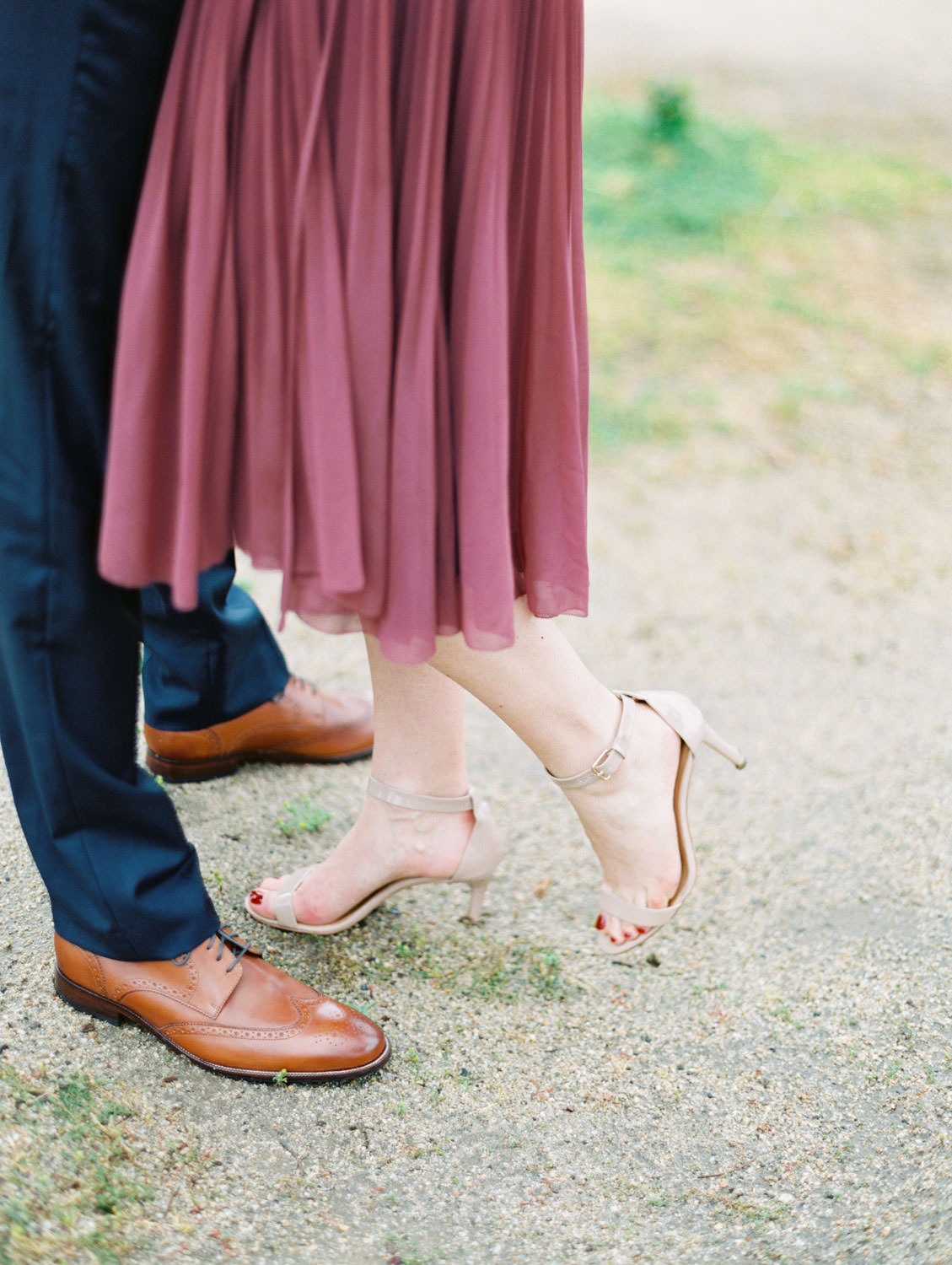 Bride in a deep mauve dress with neutral heels and groom in navy suit and brown shoes. Film Engagement Photos at Golden Gate Park by Cavin Elizabeth
