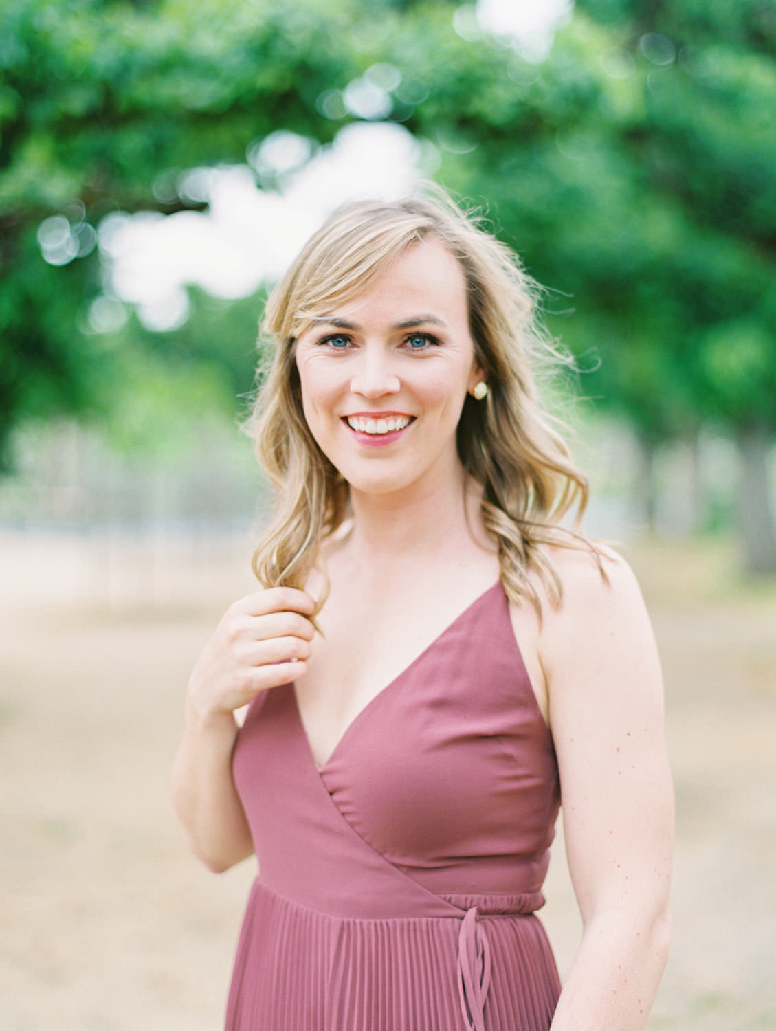 Bride in a deep mauve dress with loose curls. Film Engagement Photos at Golden Gate Park by Cavin Elizabeth