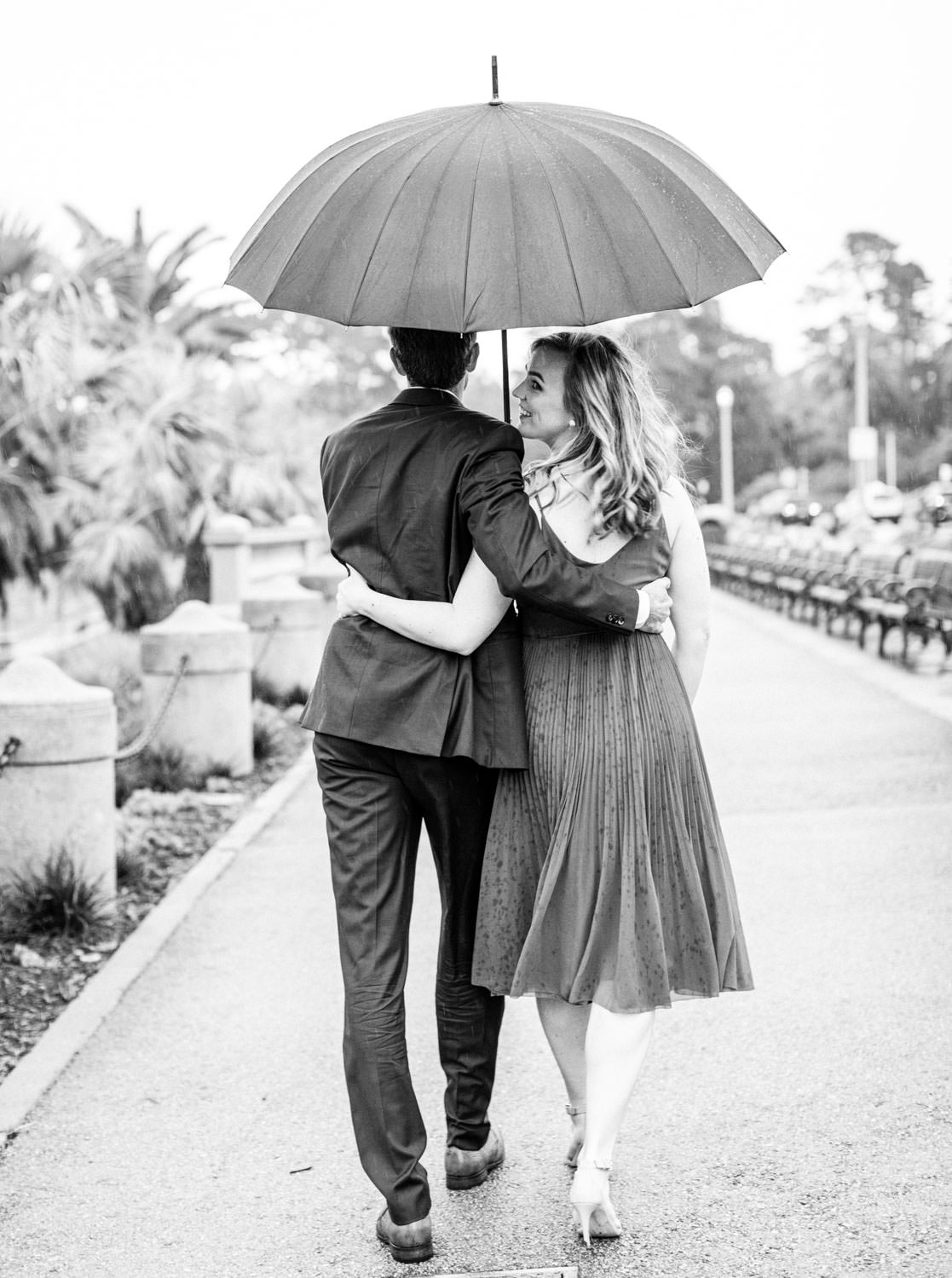 Bride in a deep mauve dress and groom in navy suit walking through a park while it's raining with an umbrella. Black and white Engagement Photos at Golden Gate Park by Cavin Elizabeth