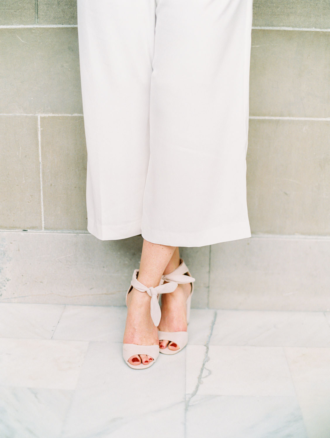 Bride in white linen jumpsuit with neutral ankle tie heels. Film Engagement Photos at San Francisco City Hall by Cavin Elizabeth