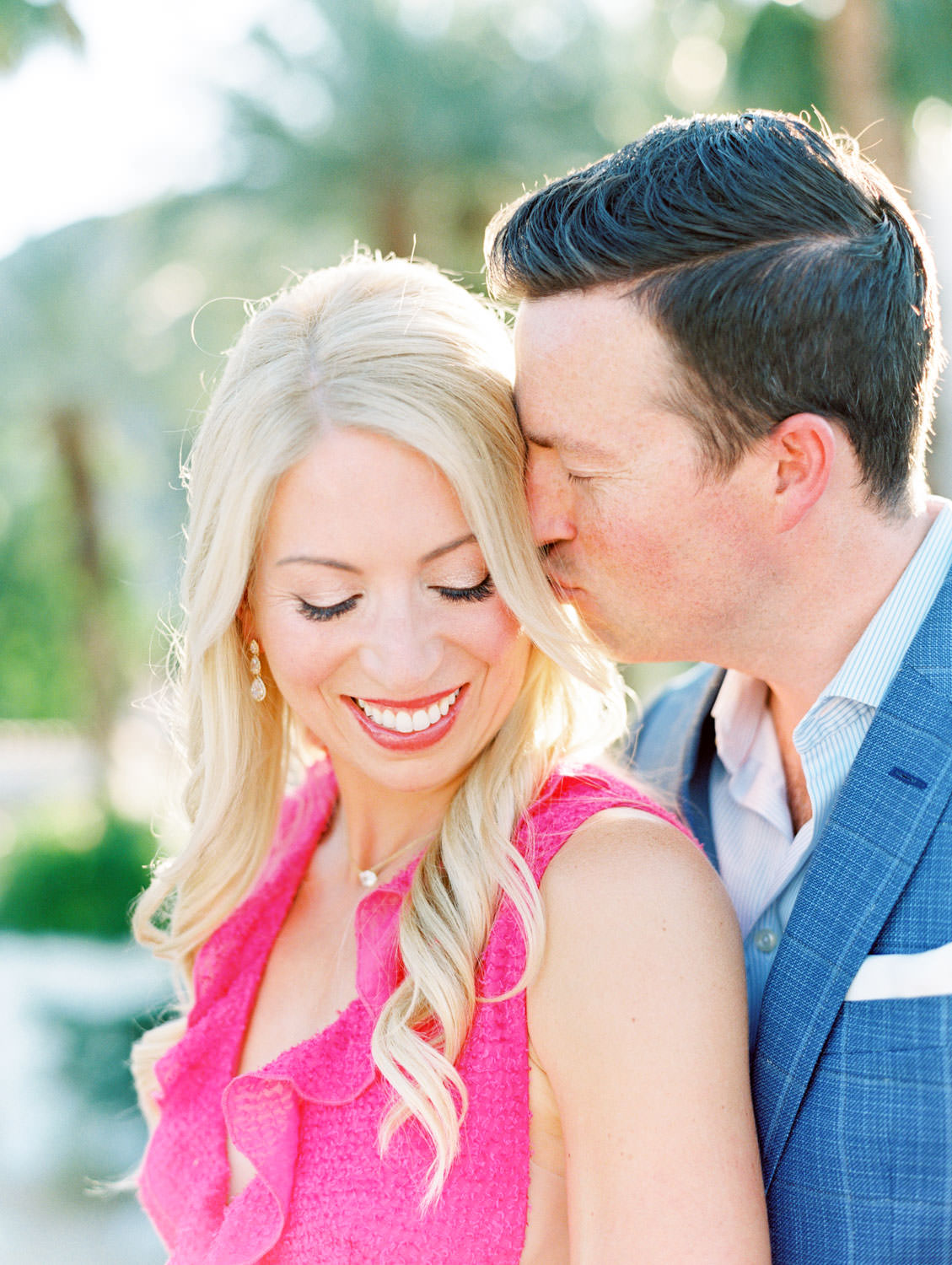 Bride in long pink ruffle dress and groom in blue suit snuggling on a rooftop. La Quinta Resort Photos on Film by Cavin Elizabeth Photography