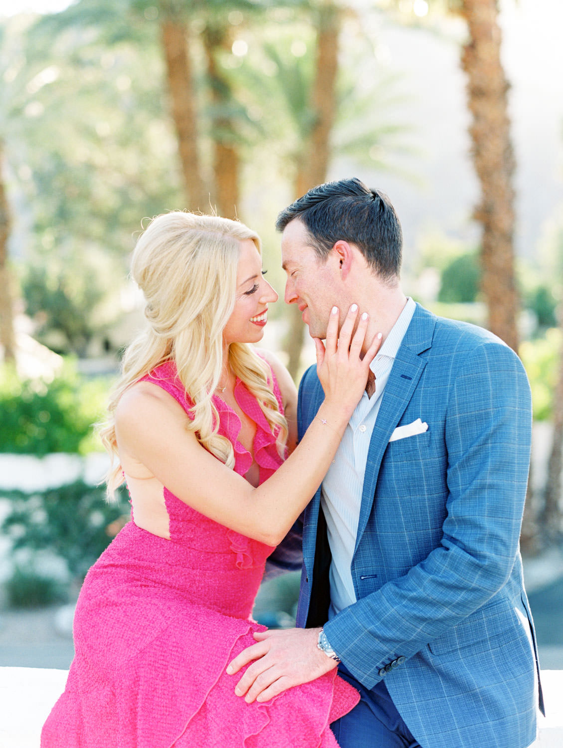 Bride in long pink ruffle dress and groom in blue suit snuggling on a rooftop. La Quinta Resort Engagement Photos on Film by Cavin Elizabeth Photography