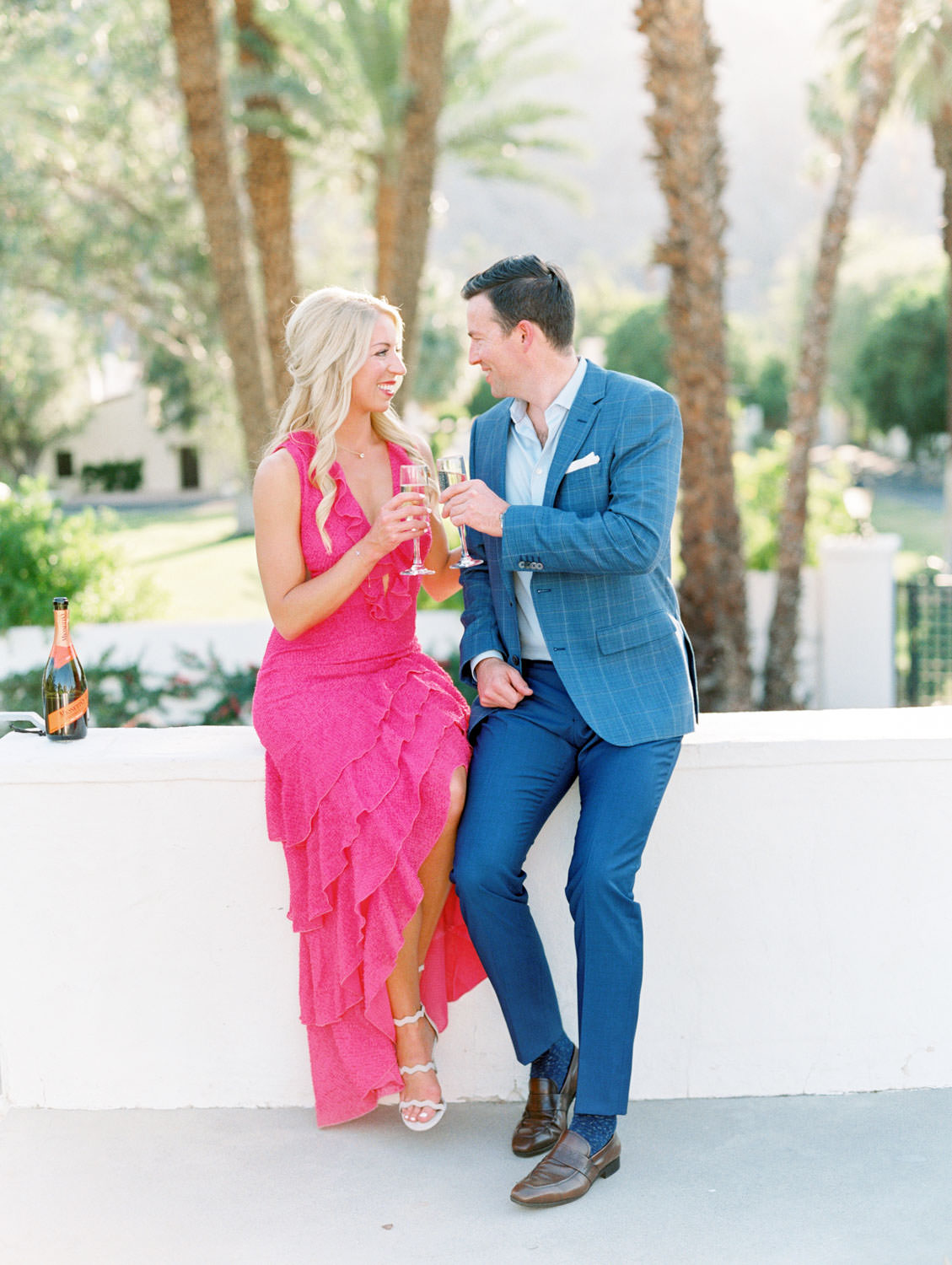 Bride in long pink ruffle dress and groom in blue suit drinking champagne on a rooftop. La Quinta Resort Engagement Photos on Film by Cavin Elizabeth Photography