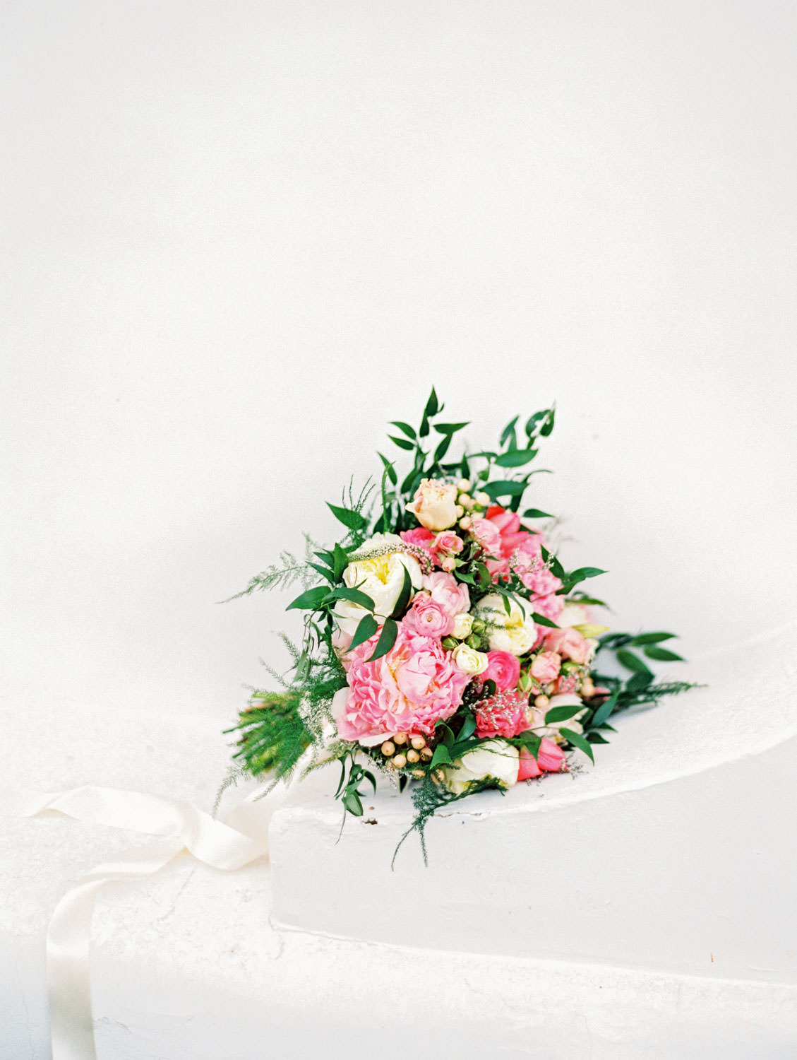 Large engagement bouquet with pink, ivory, and soft yellow flowers mixed with greenery and tied with an ivory silk ribbon shot against a white wall. La Quinta Resort Engagement Photos on Film by Cavin Elizabeth Photography