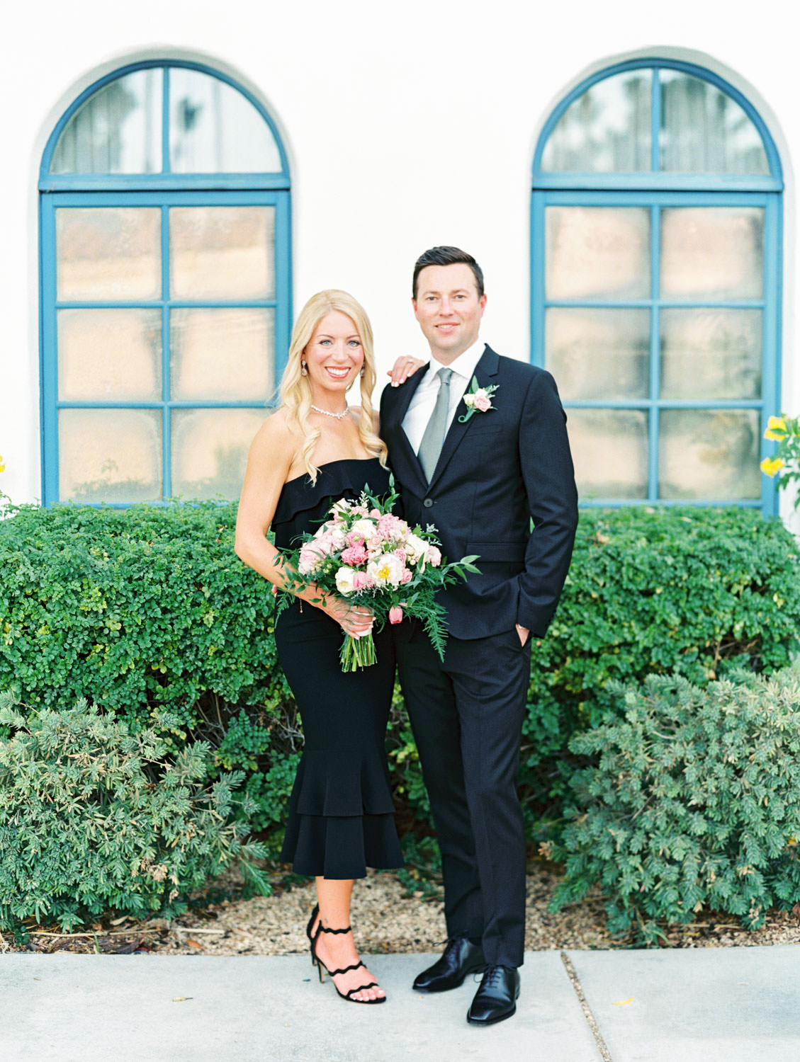 Bride in black strapless dress and black heels and groom in black suit in front of a gorgeous villa with blue windows. La Quinta Resort Engagement Photos on Film by Cavin Elizabeth Photography