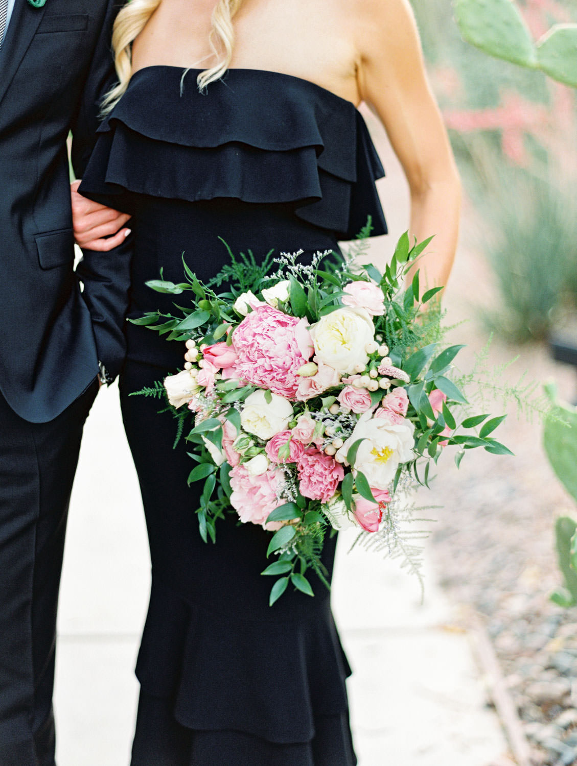 Bride holding ivory, pink, and green bouquet wearing a black strapless dress and black heels and groom in black suit. La Quinta Resort Engagement Photos on Film by Cavin Elizabeth Photography