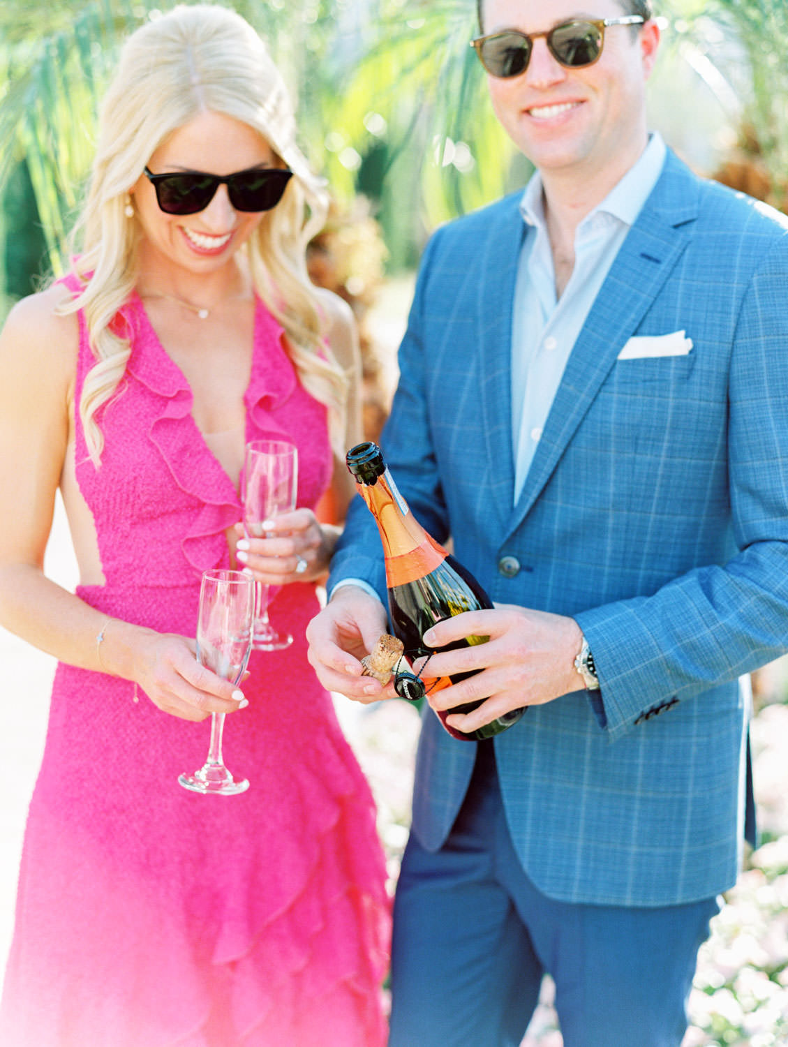 Bride in long pink ruffle dress and groom in blue suit with champagne. La Quinta Resort Engagement Photos on Film by Cavin Elizabeth Photography