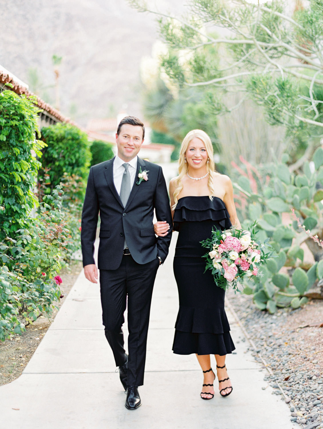 Bride holding ivory, pink, and green bouquet wearing a black strapless dress and black heels and groom in black suit in a cactus garden. La Quinta Resort Engagement Photos on Film by Cavin Elizabeth Photography