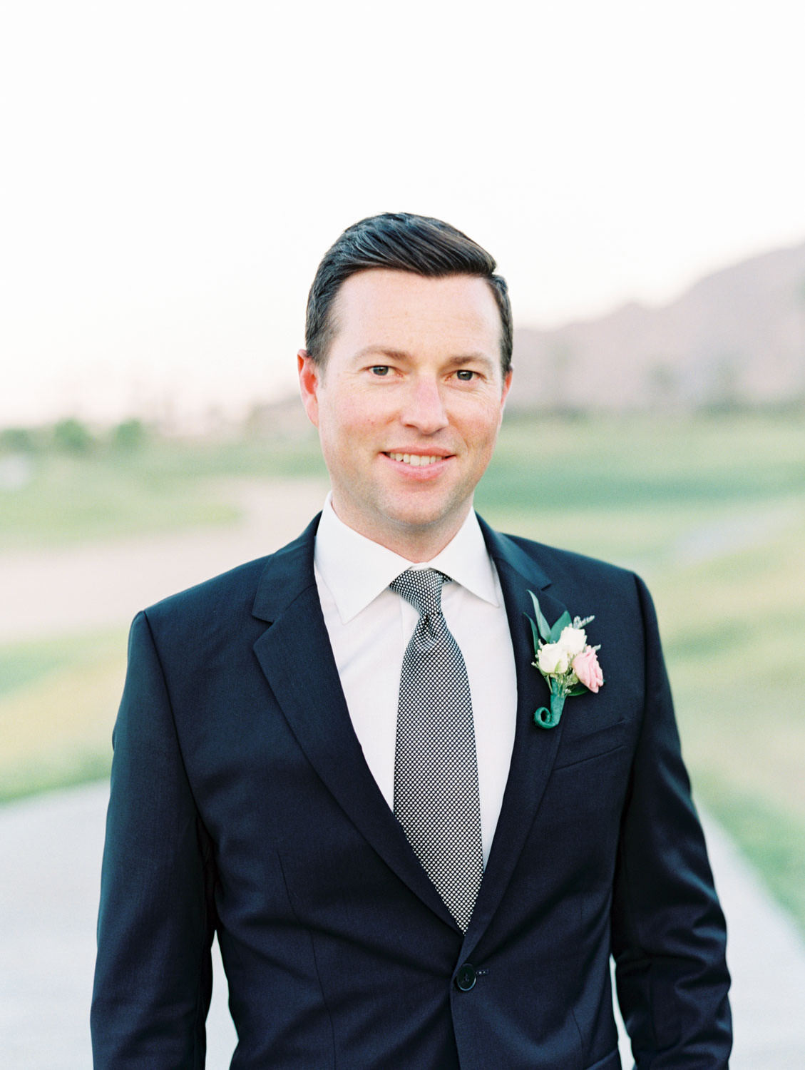 Groom in black suit with a pink and ivory boutonniere. La Quinta Resort Engagement Photos on Film by Cavin Elizabeth Photography