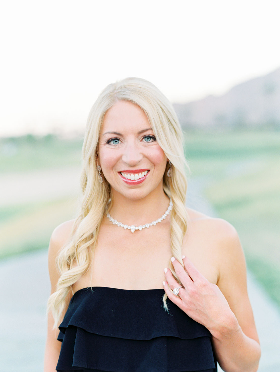 Bride in a strapless fitted black dress with hair curled and down. La Quinta Resort Engagement Photos on Film by Cavin Elizabeth Photography