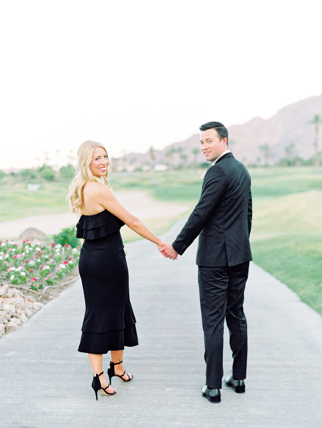 Groom in black suit with the bride in a strapless fitted black dress and black heels on a golf course with large mountain views. La Quinta Resort Engagement Photos on Film by Cavin Elizabeth Photography