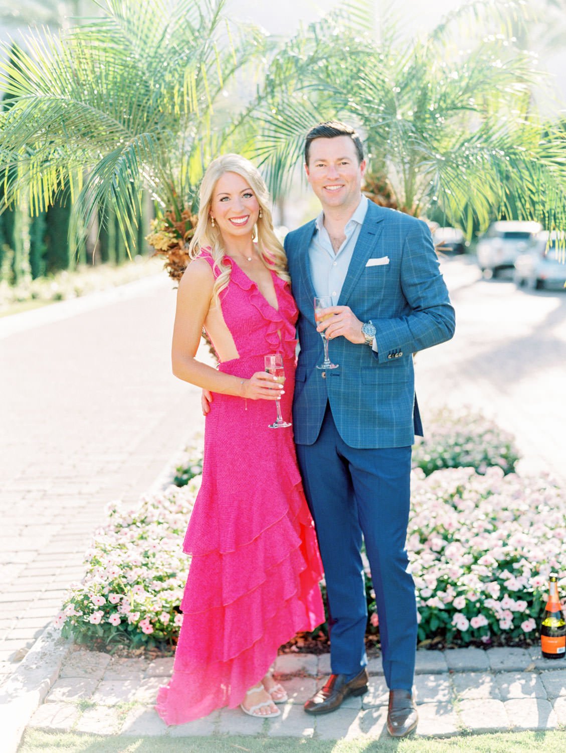Bride in long pink ruffle dress and groom in blue suit with champagne. formal engagement outfits. La Quinta Resort Engagement Photos on Film by Cavin Elizabeth Photography