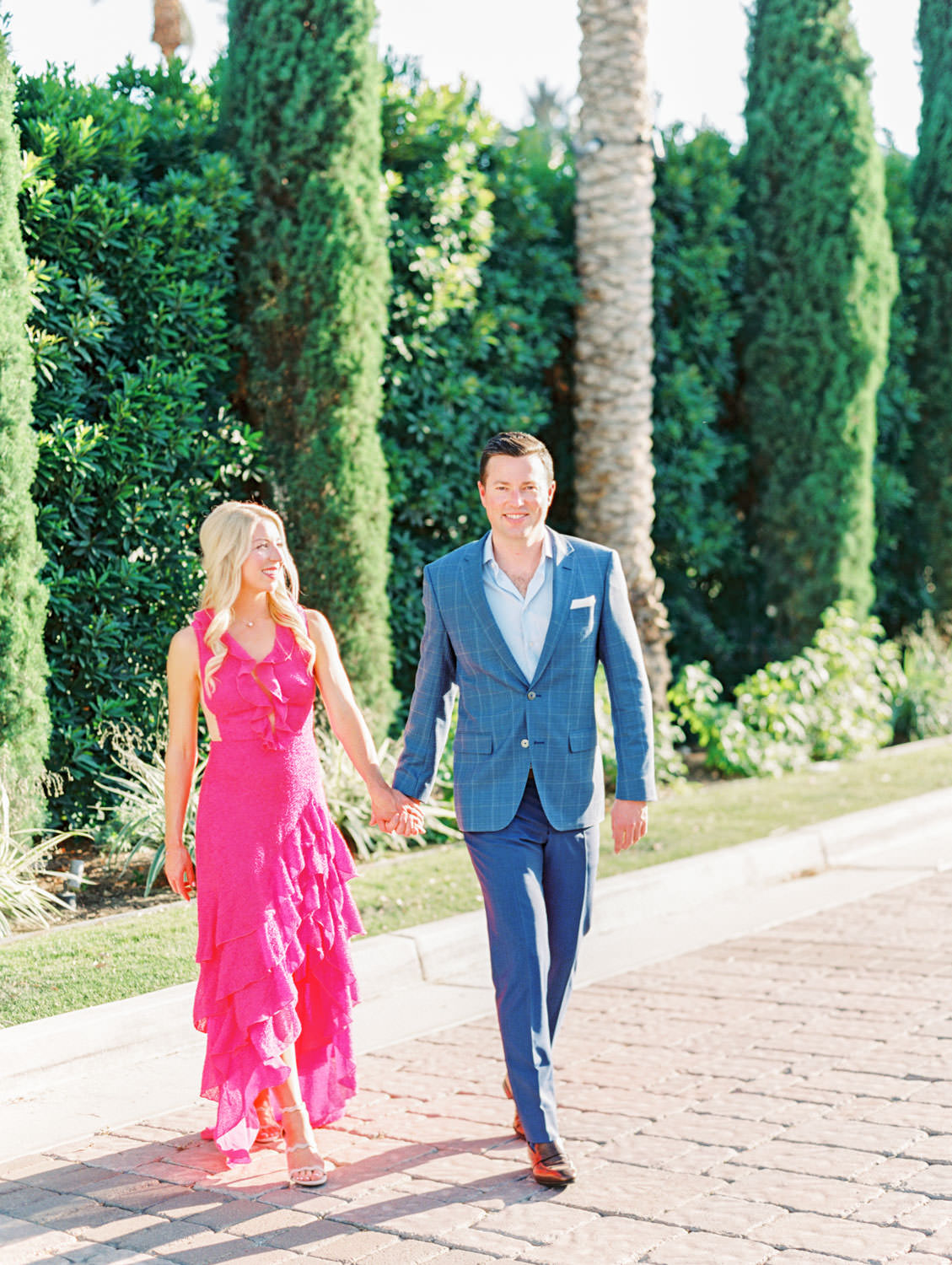 Bride in long pink ruffle dress and groom in blue suit walking by cyprus trees. La Quinta Resort Engagement Photos on Film by Cavin Elizabeth Photography