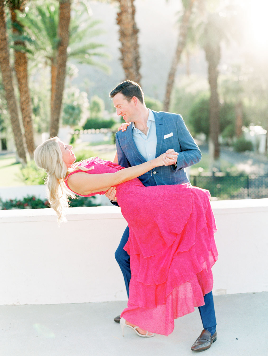 Bride in long pink ruffle dress and groom in blue suit dancing on a rooftop. La Quinta Resort Engagement Photos on Film by Cavin Elizabeth Photography