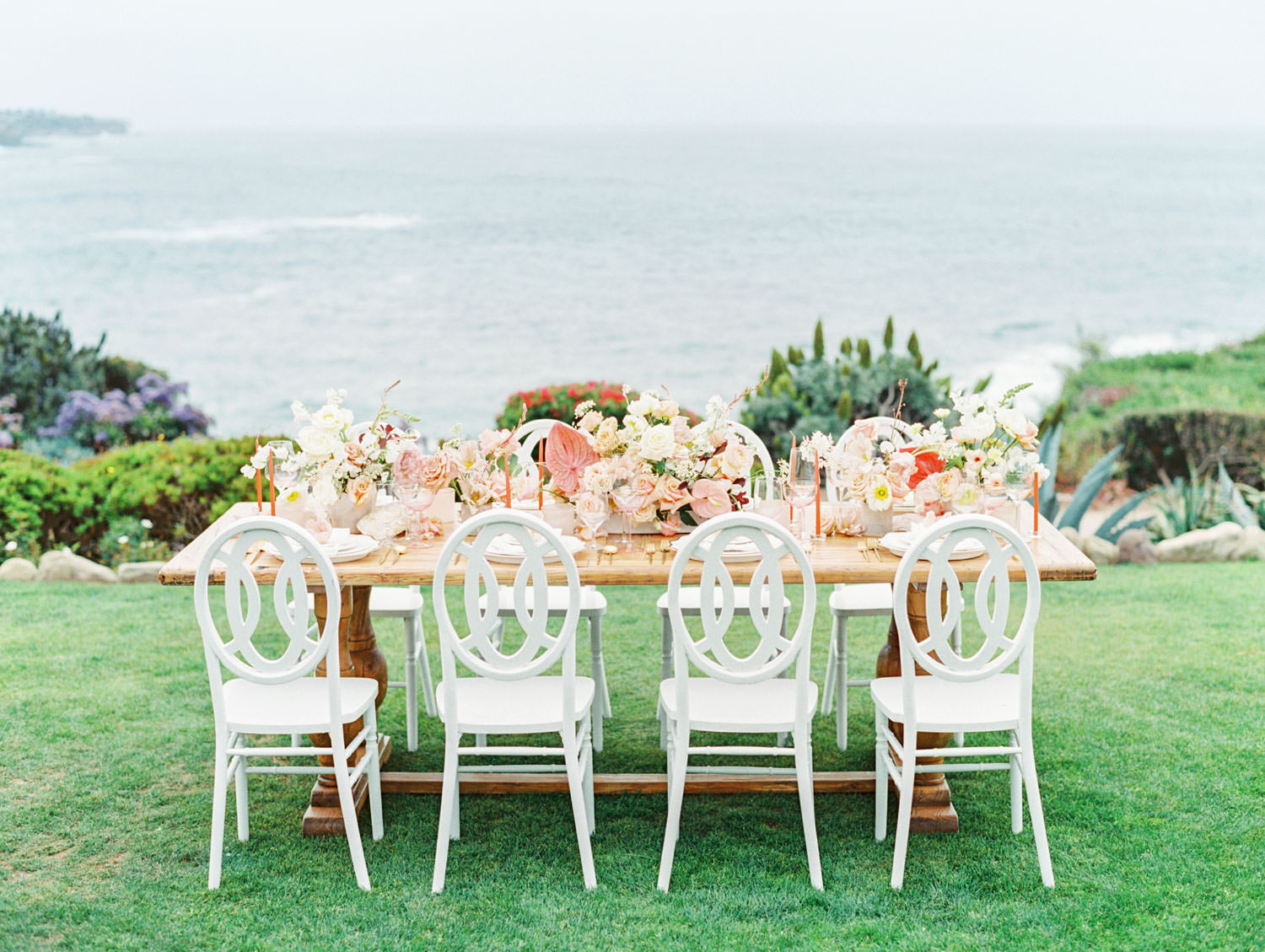 Reception table with white chairs and blend of whites, blush and mauve with neutral coastal elements like coral and sea glass and an ocean backdrop. Coastal Montage Laguna Beach Wedding Editorial by Cavin Elizabeth on film
